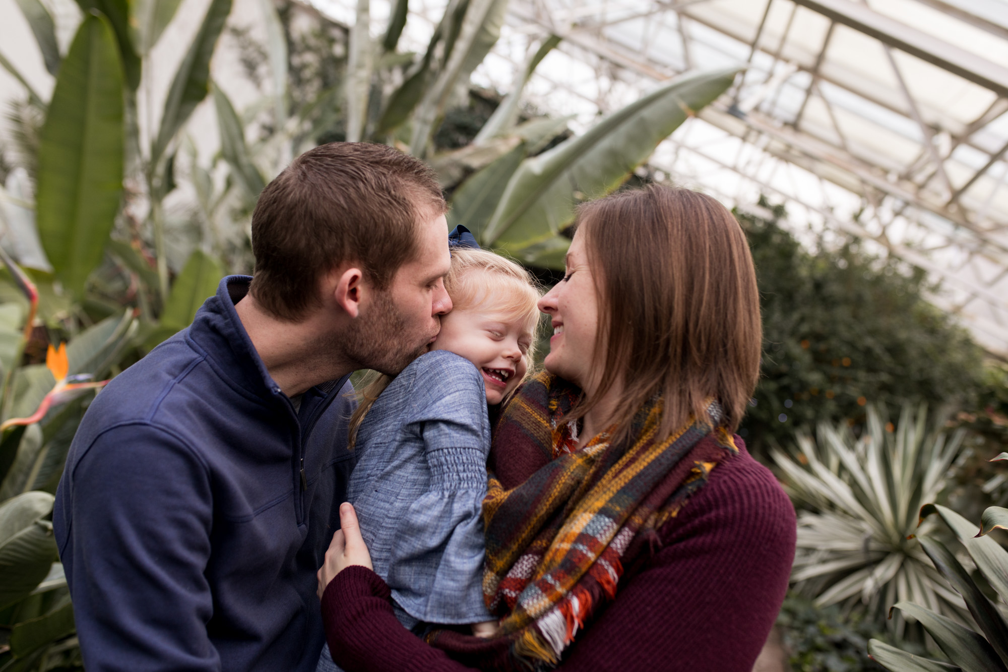 mom and dad kiss daughter's cheeks during Fort Wayne family photography session at Foellinger-Freimann Botanical Conservatory
