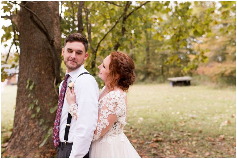 bride hugs groom behind back during wedding portraits at The Barn in Zionsville