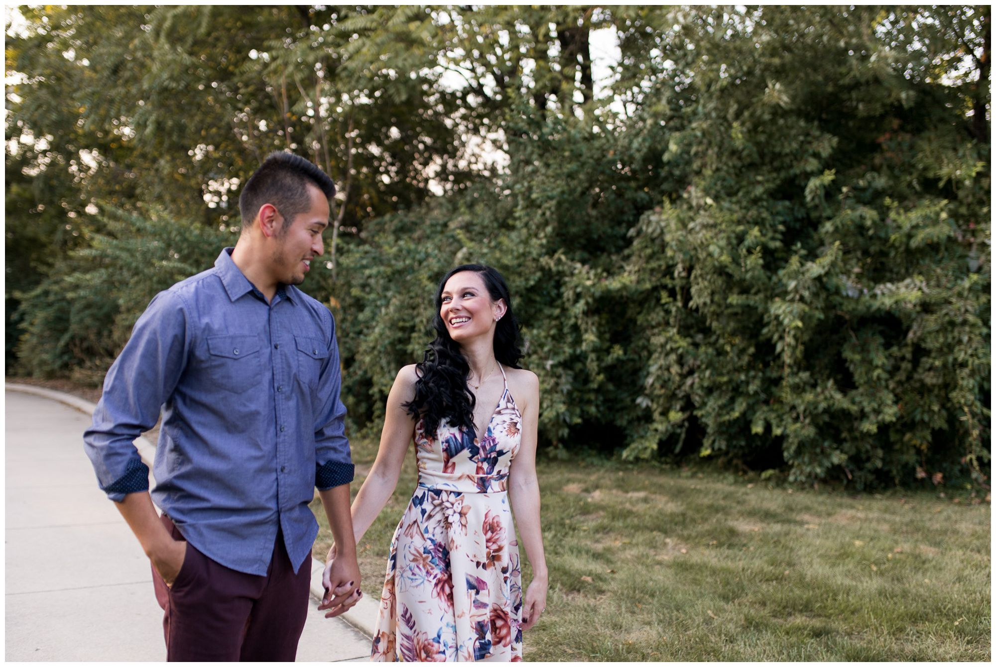 couple walks holding hands during engagement session at Headwaters Park in Fort Wayne Indiana