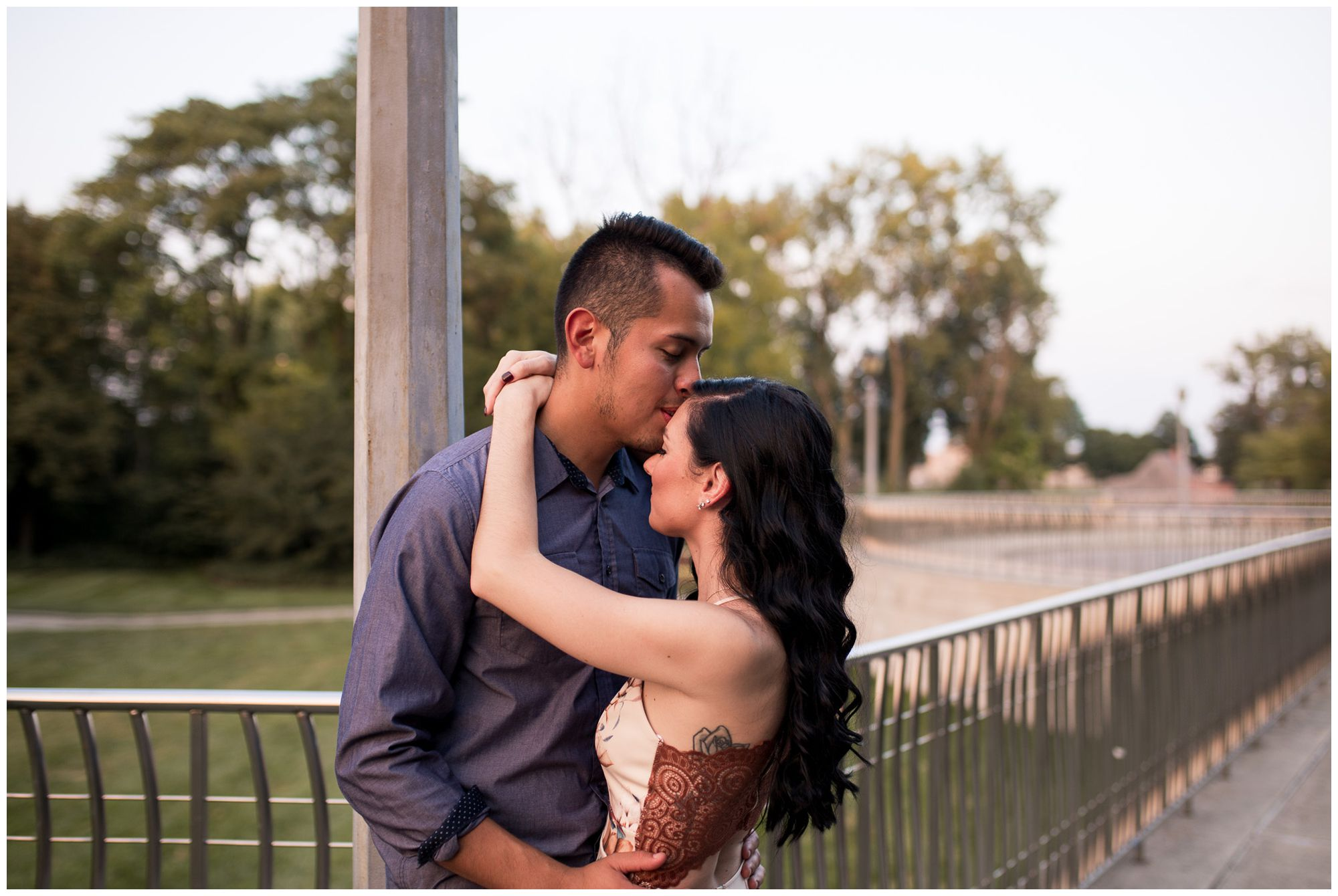 groom kisses bride's head during engagement session at Headwaters Park in Fort Wayne