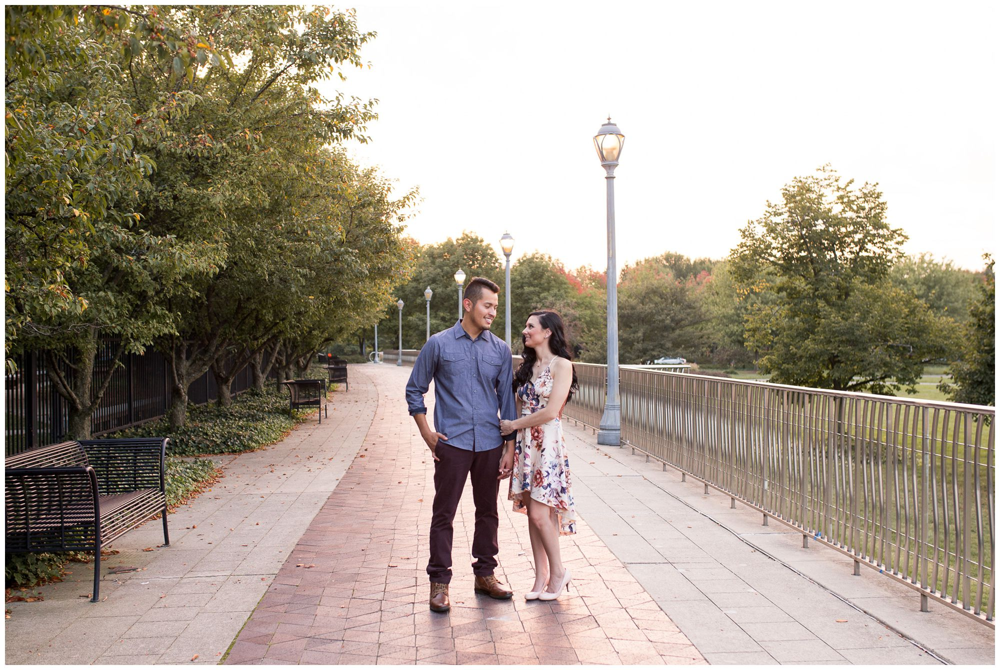 couple hold hand on bridge during Fort Wayne engagement session at Headwaters Park