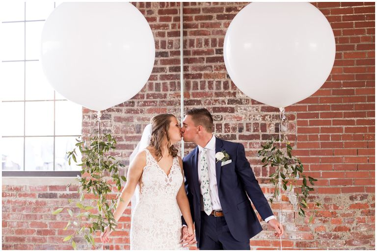 bride and groom kiss holding balloons during portraits at INDUSTRY venue in downtown Indianapolis