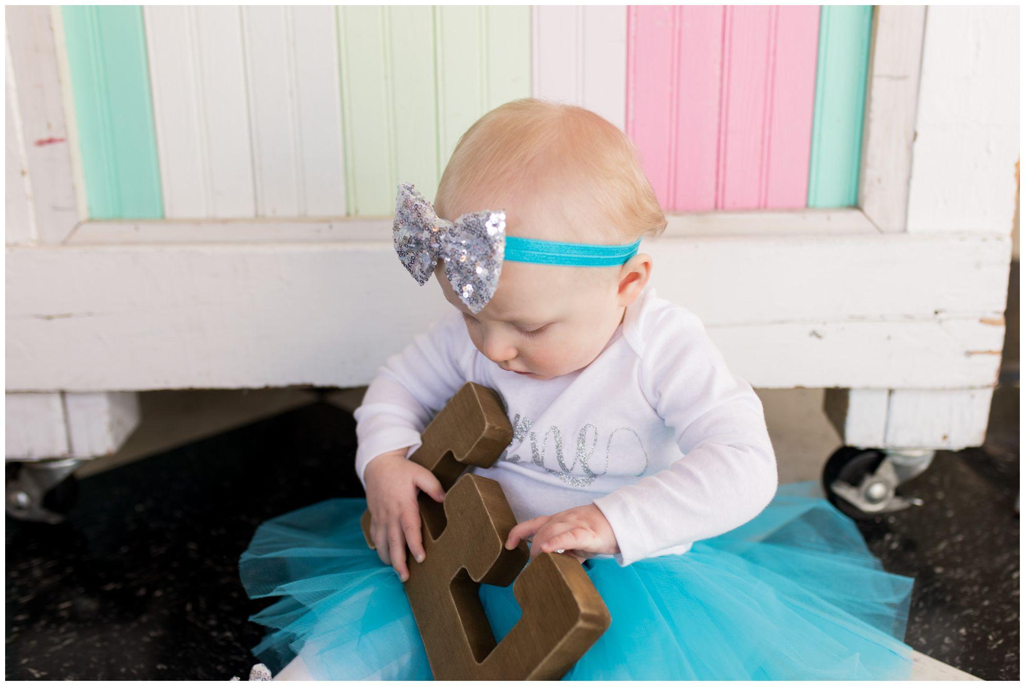 baby holds letter E during first year session at The Flying Cupcake