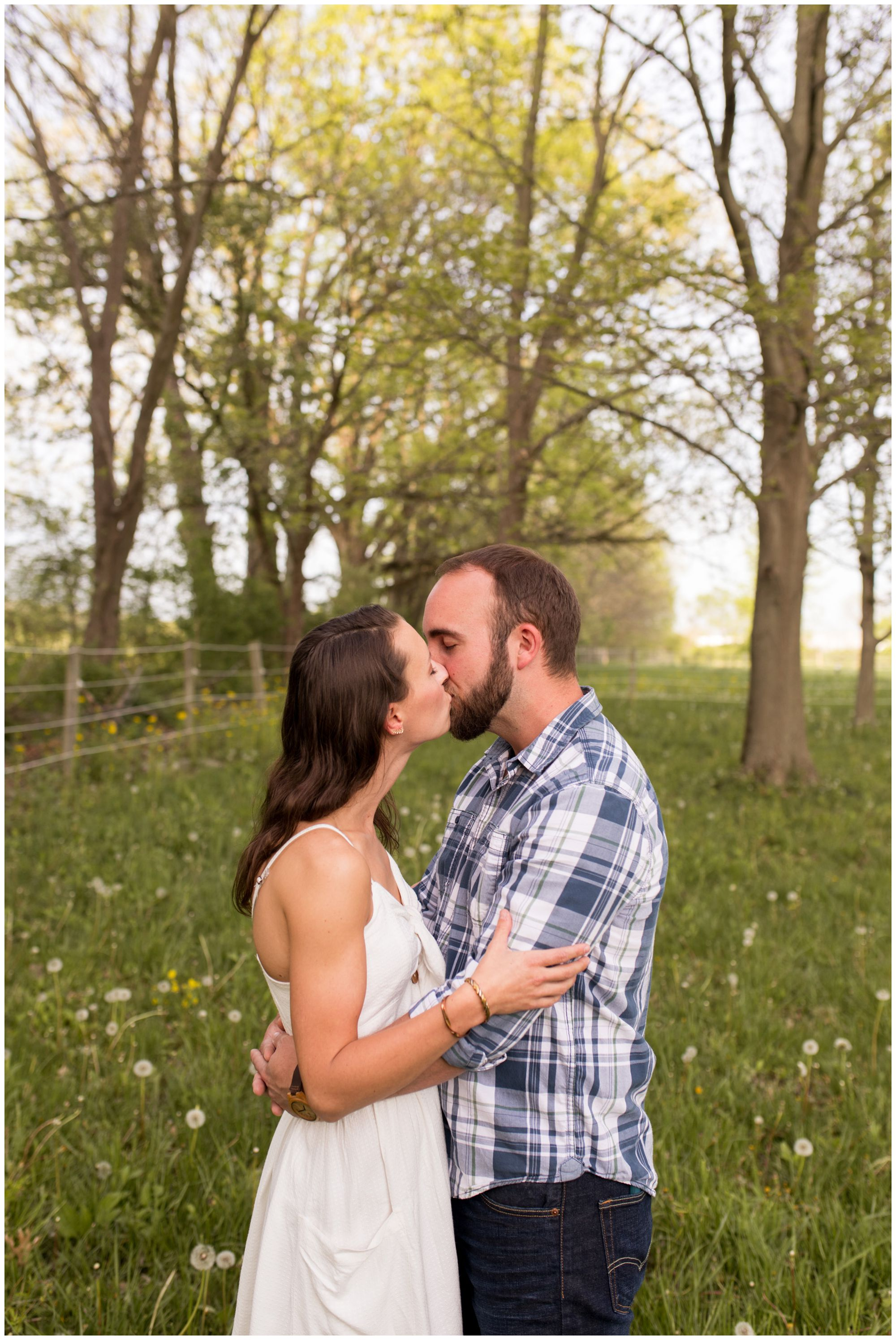 bride and groom kiss in horse pasture during engagement session in Indianapolis