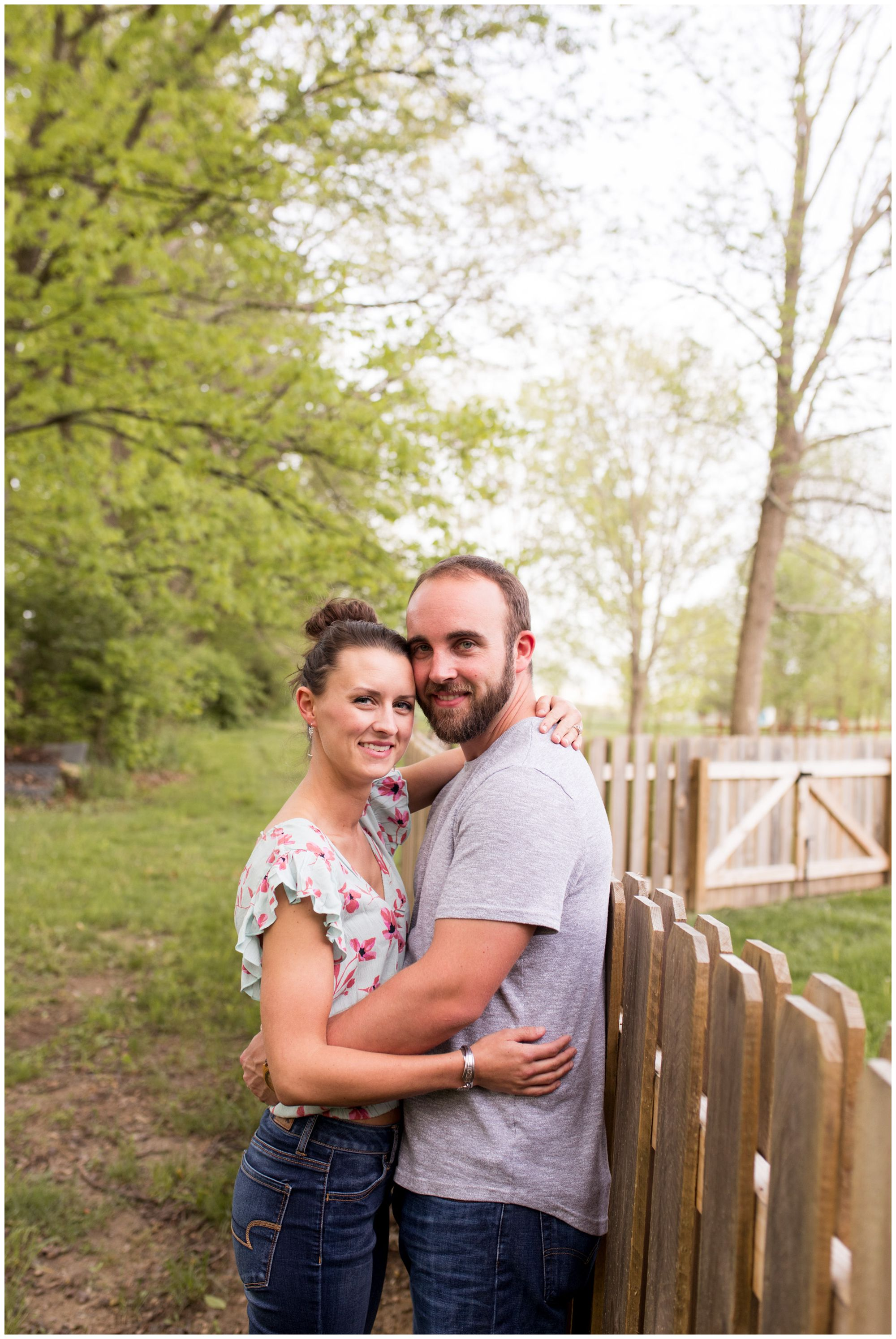 bride and groom standing against fence during Indianapolis engagement session