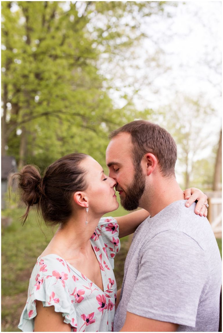 bride and groom kiss in horse pasture during Indianapolis engagement session