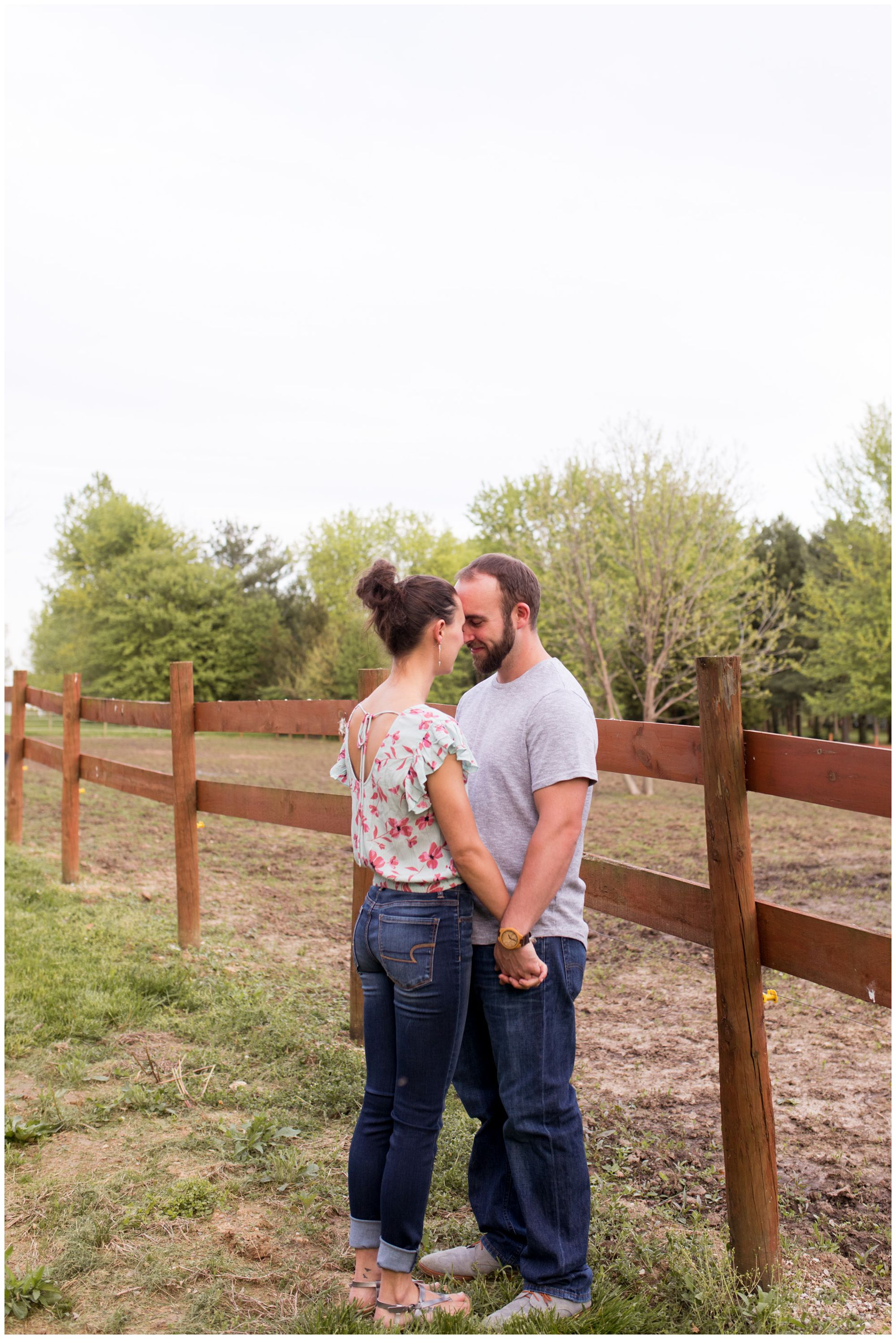 bride and groom hold hands near horse pasture fence in Indianapolis engagement session