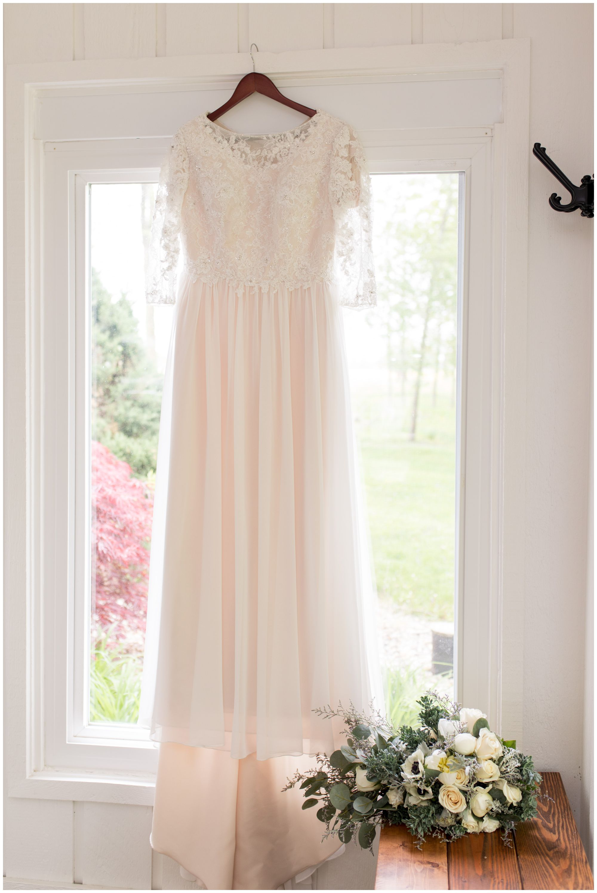 bride's wedding dress hanging in window at The Creek House at Burton Farm in Muncie Indiana