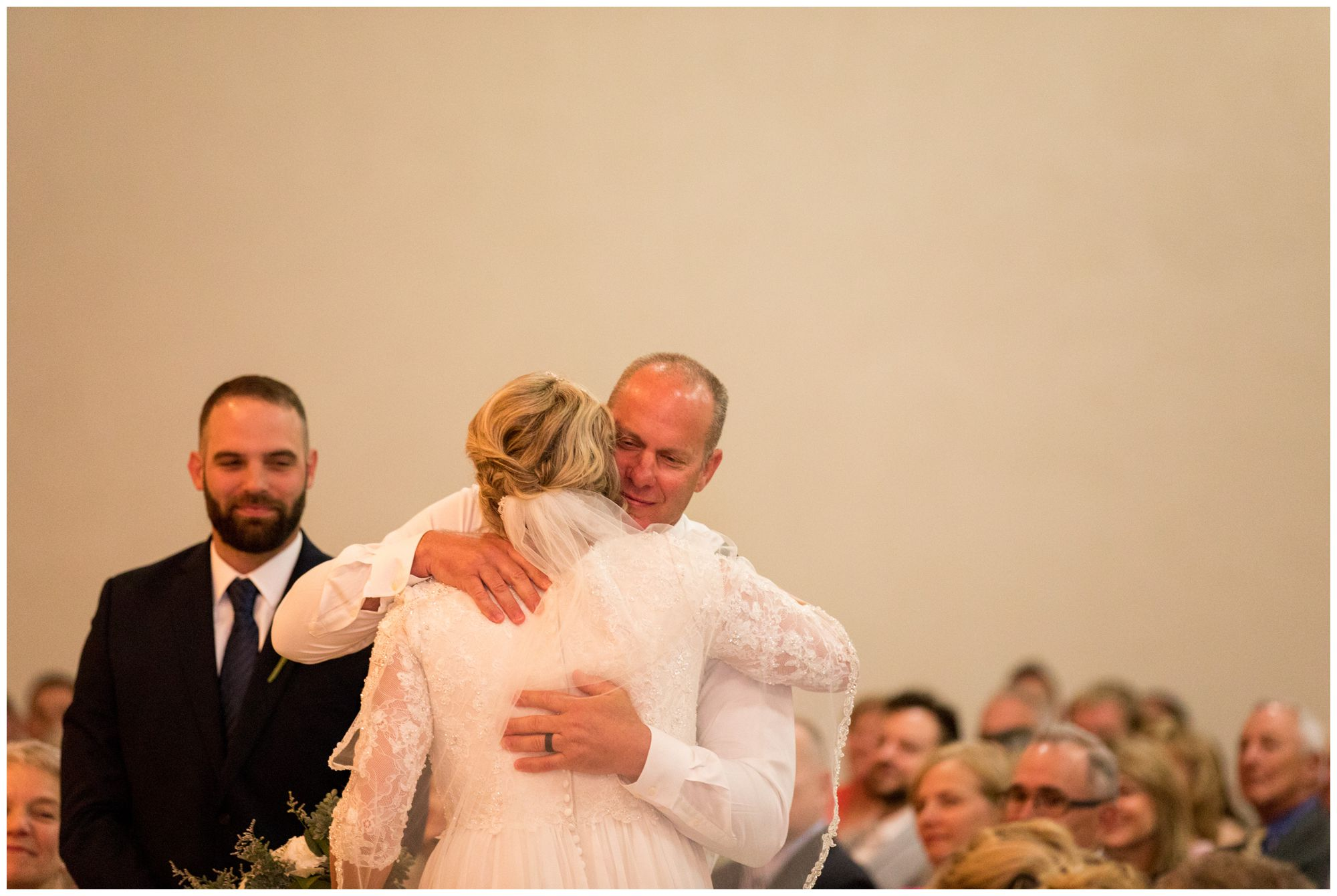 father of bride hugs daughter during wedding ceremony at Muncie First Church of the Nazarene