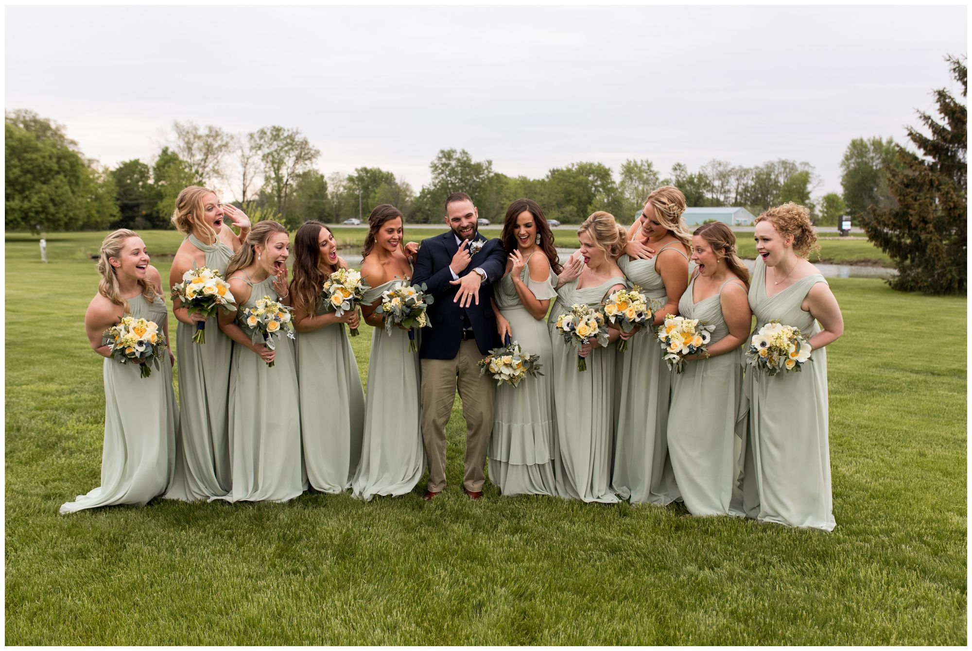 bridesmaids look at groom's wedding band during Muncie wedding party portraits