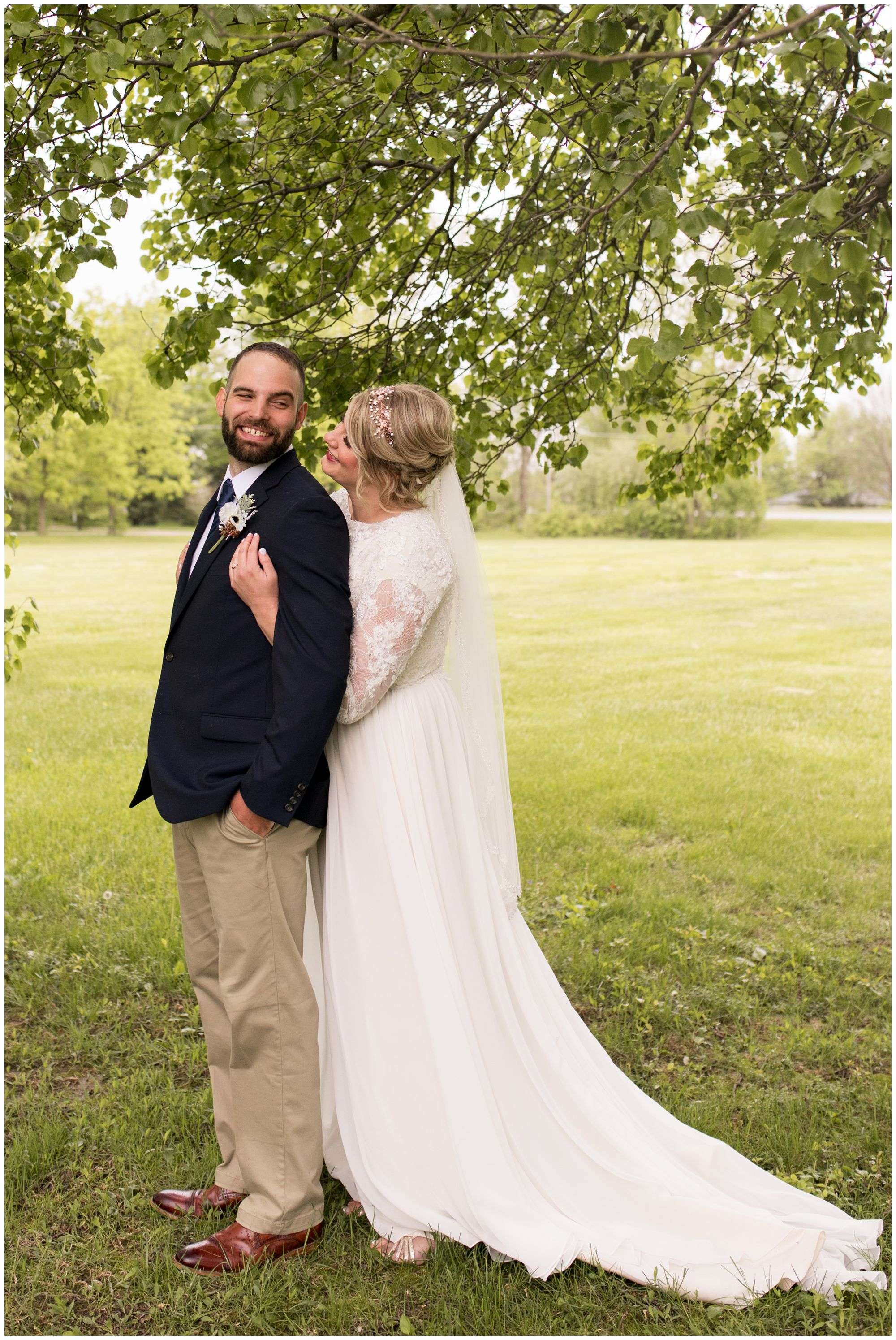 bride hugs groom from behind during portraits after Muncie wedding ceremony