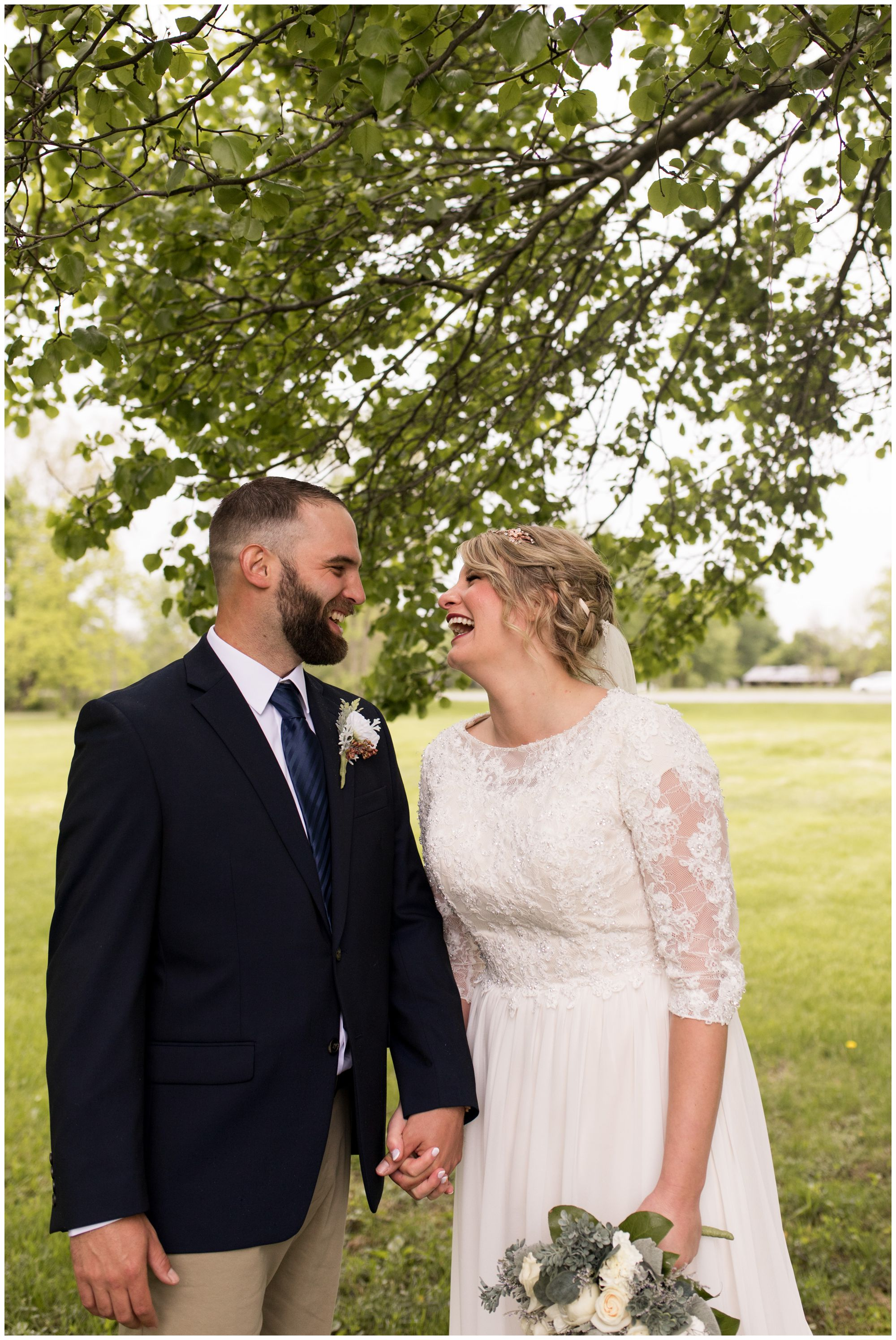 bride and groom hold hands and laugh during wedding portraits after Muncie Indiana ceremony