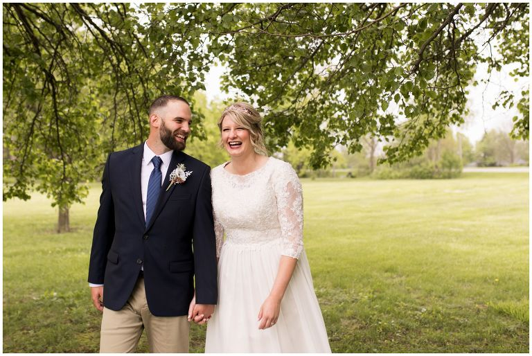 bride and groom walk and laugh together during portraits after wedding ceremony in Muncie Indiana
