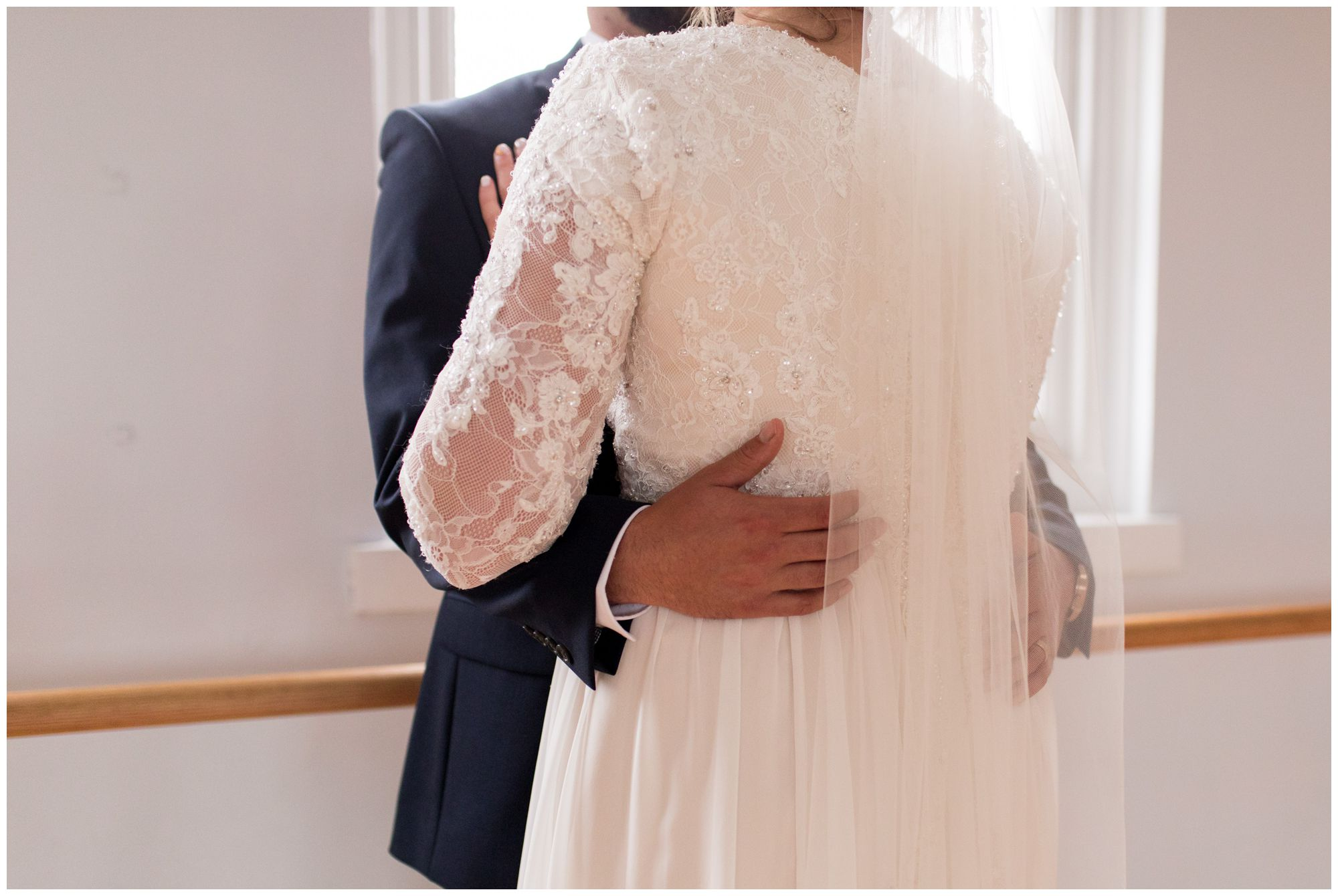 groom's hands wrapped around bride's back during wedding portraits at Cornerstone Center for the Arts