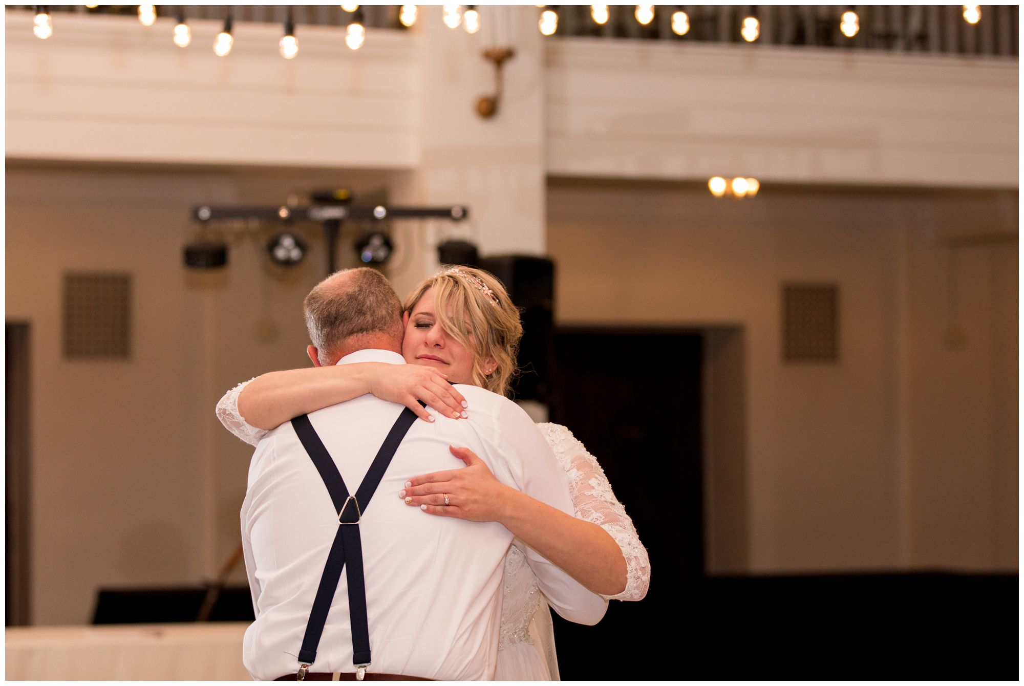 bride hugs dad after dancing together during Cornerstone Center for the Arts wedding reception in Muncie Indiana
