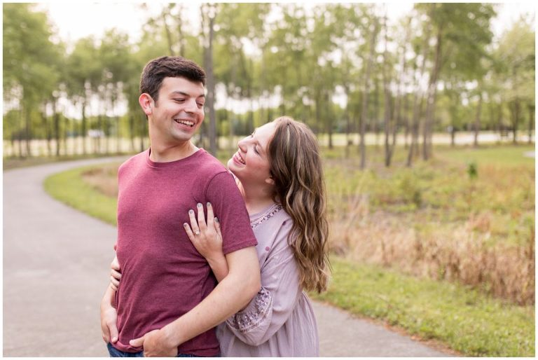 bride hugs groom from behind during engagement session at Prophetstown State Park in Lafayette Indiana