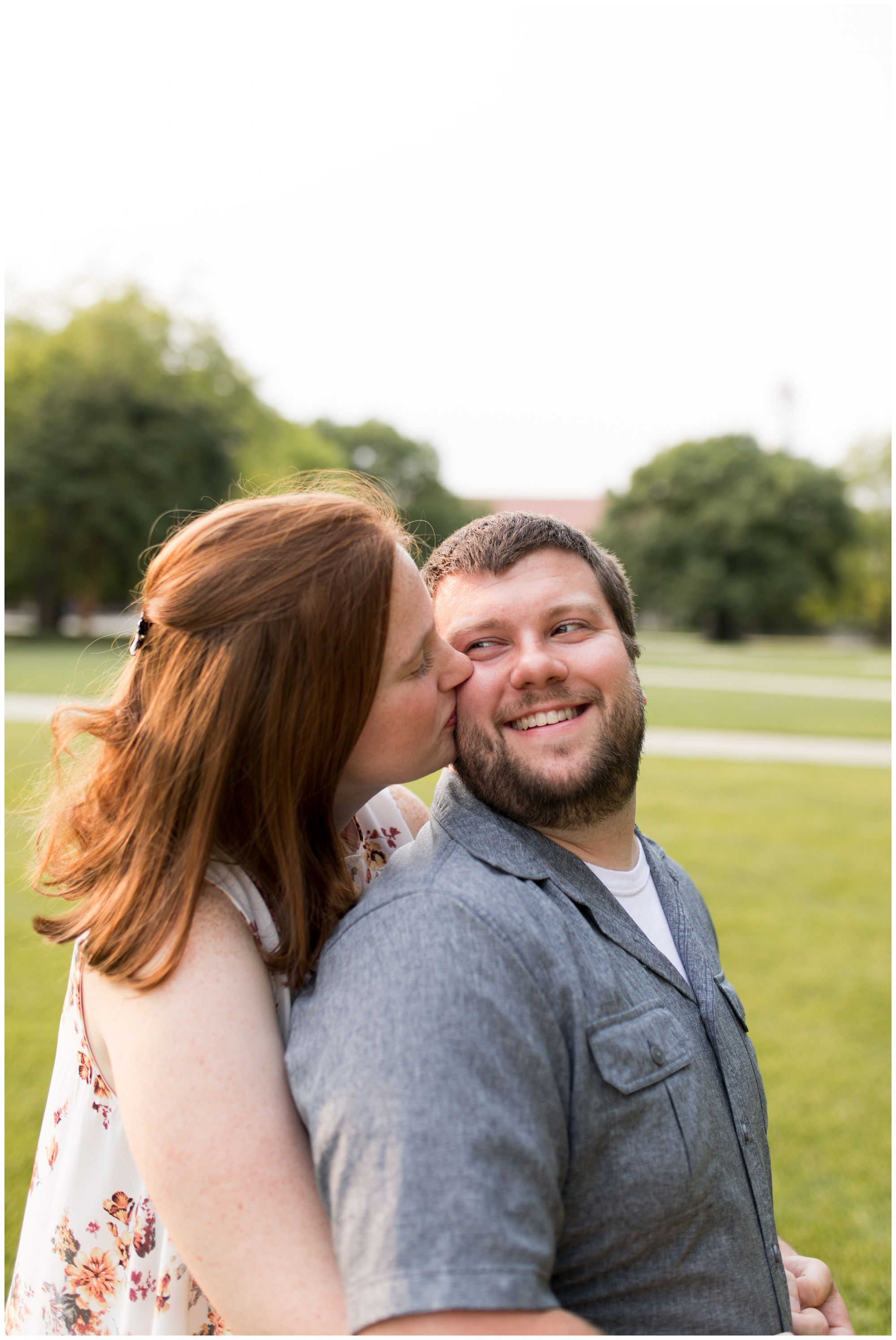 bride kisses groom on cheek during Purdue University engagement session in Lafayette, Indiana