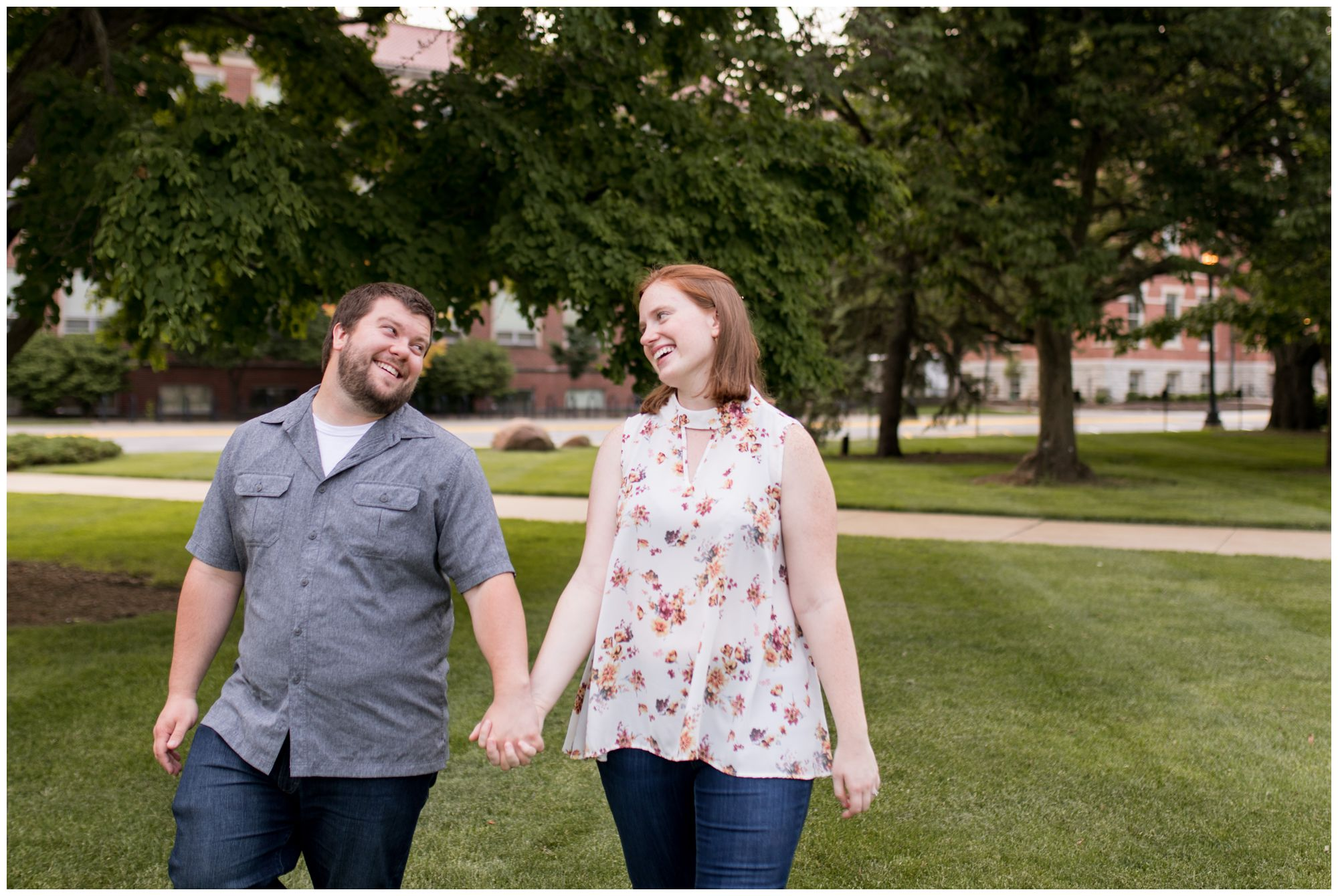 couple walks during Purdue University engagement session in West Lafayette Indiana