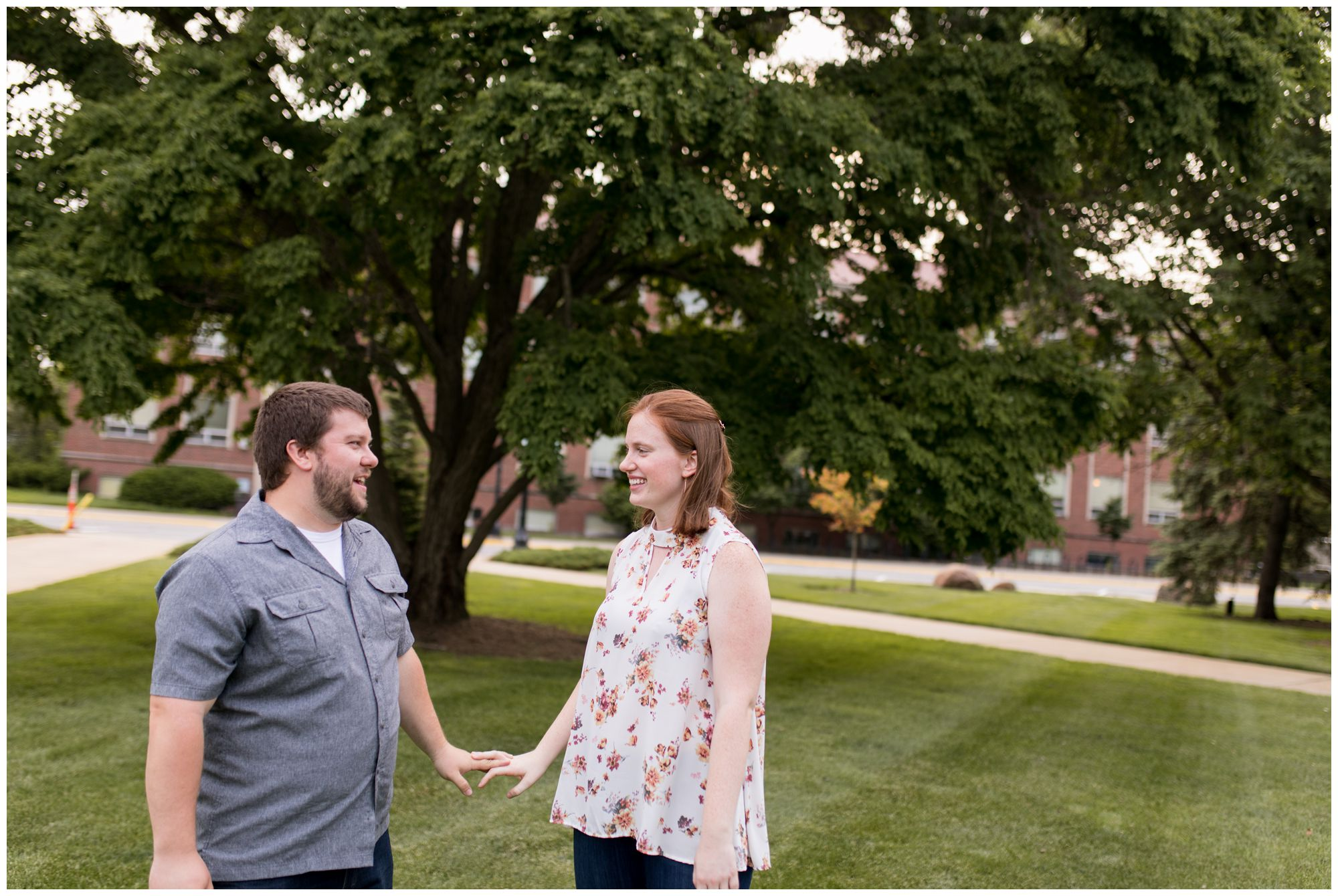 couple hold hands during Purdue University engagement session in West Lafayette, Indiana
