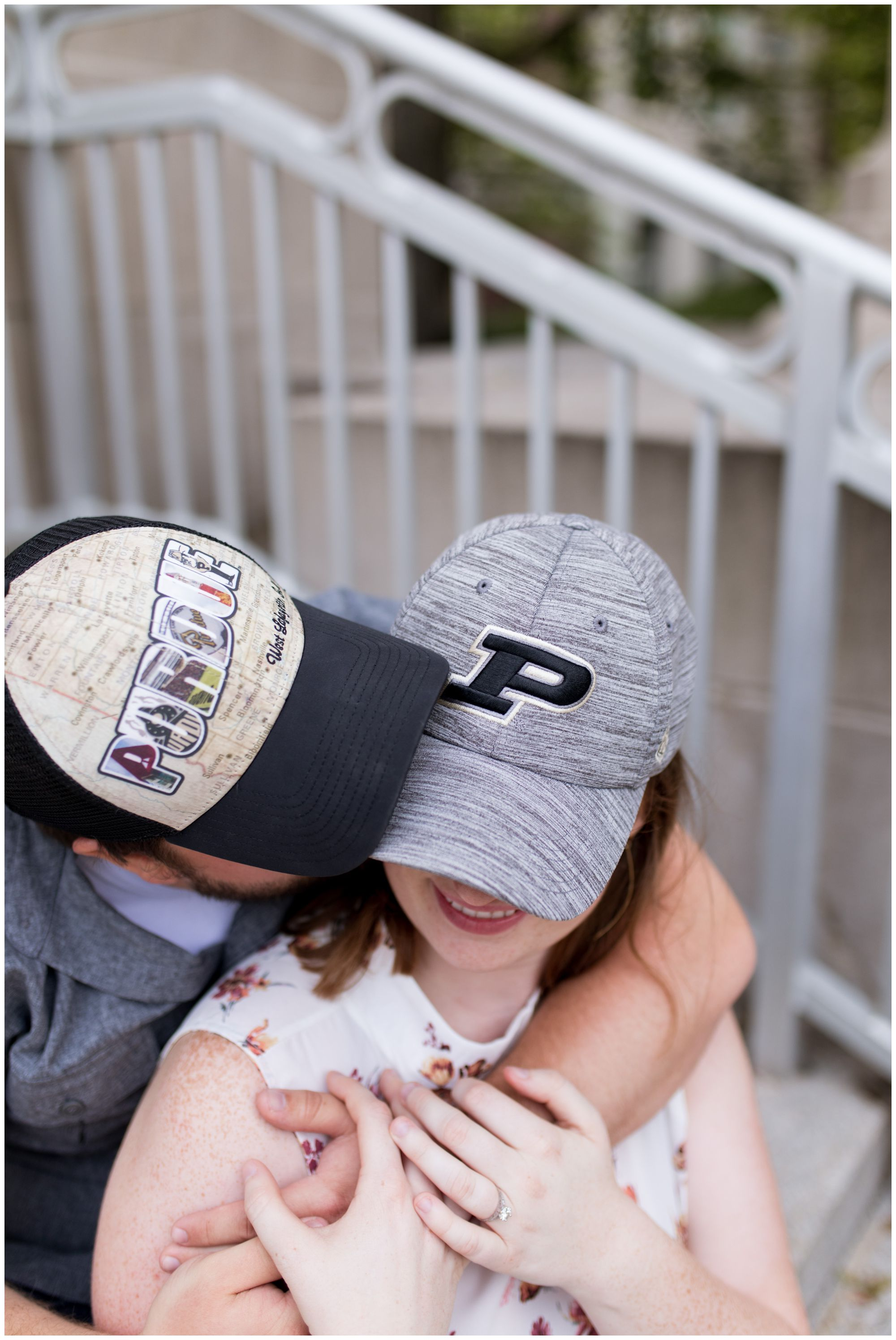 groom kisses bride's cheek wearing Purdue hats during engagement session