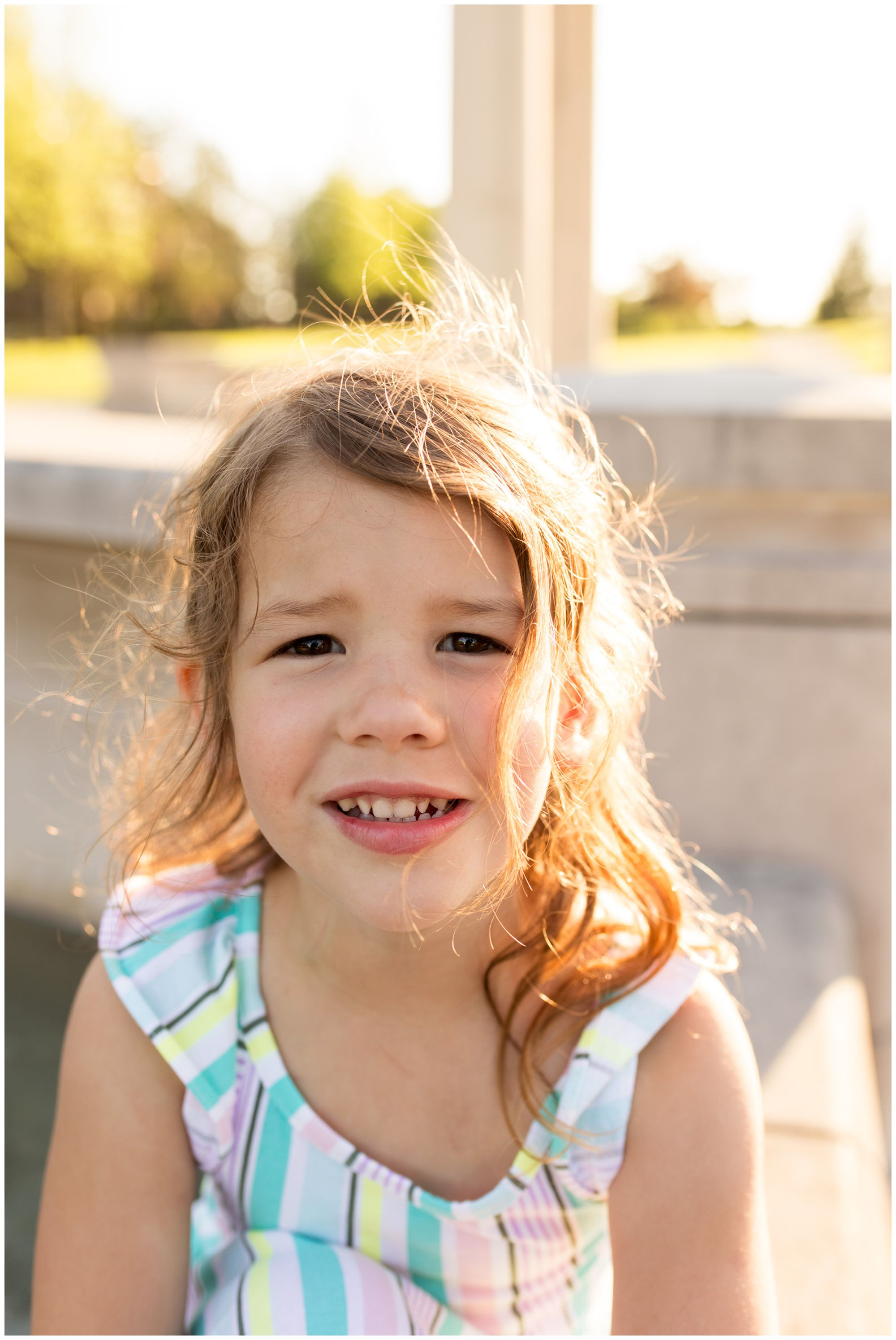 little girl smiling at camera at Coxhall Gardens during family session