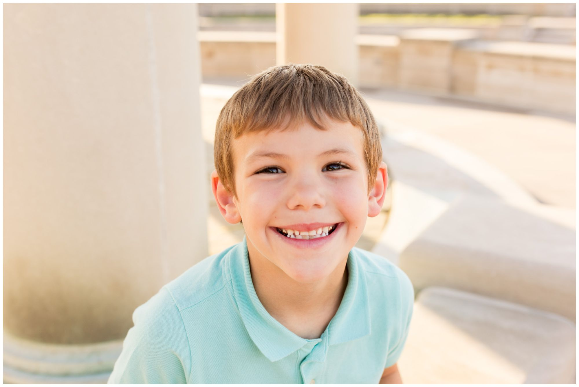 boy smiling at camera during family session at Coxhall Gardens in Carmel, Indiana