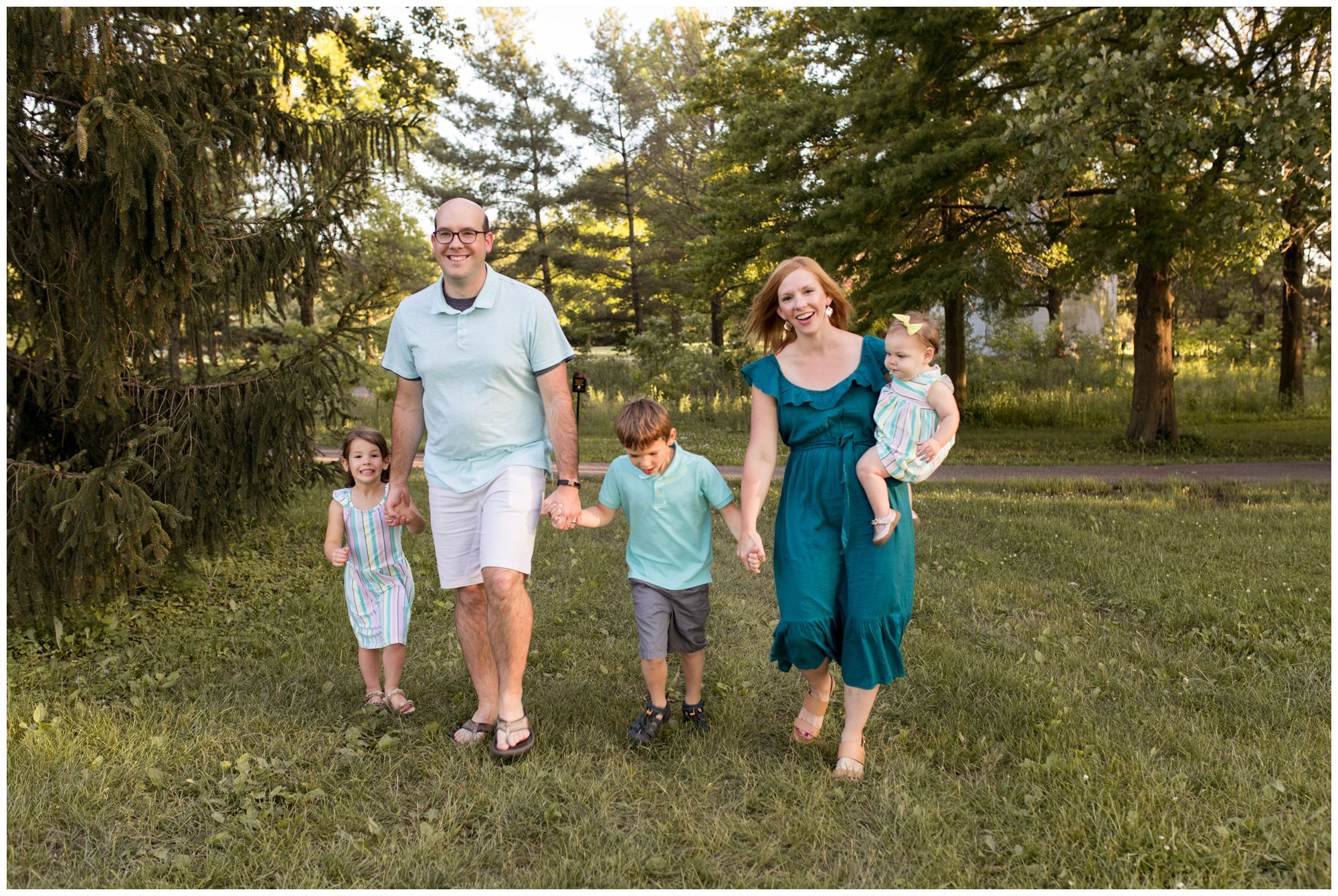 family holding hands and walking during Coxhall Gardens photo session in Carmel Indiana