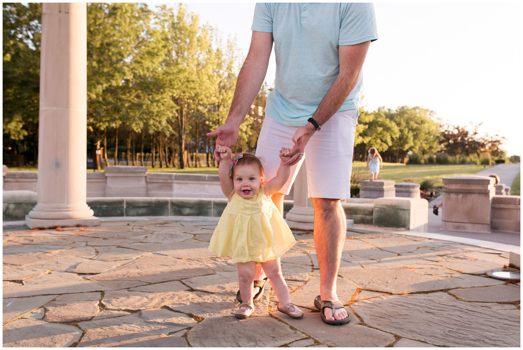 dad holding little girl's hand while she walks at Coxhall Gardens in Carmel Indiana