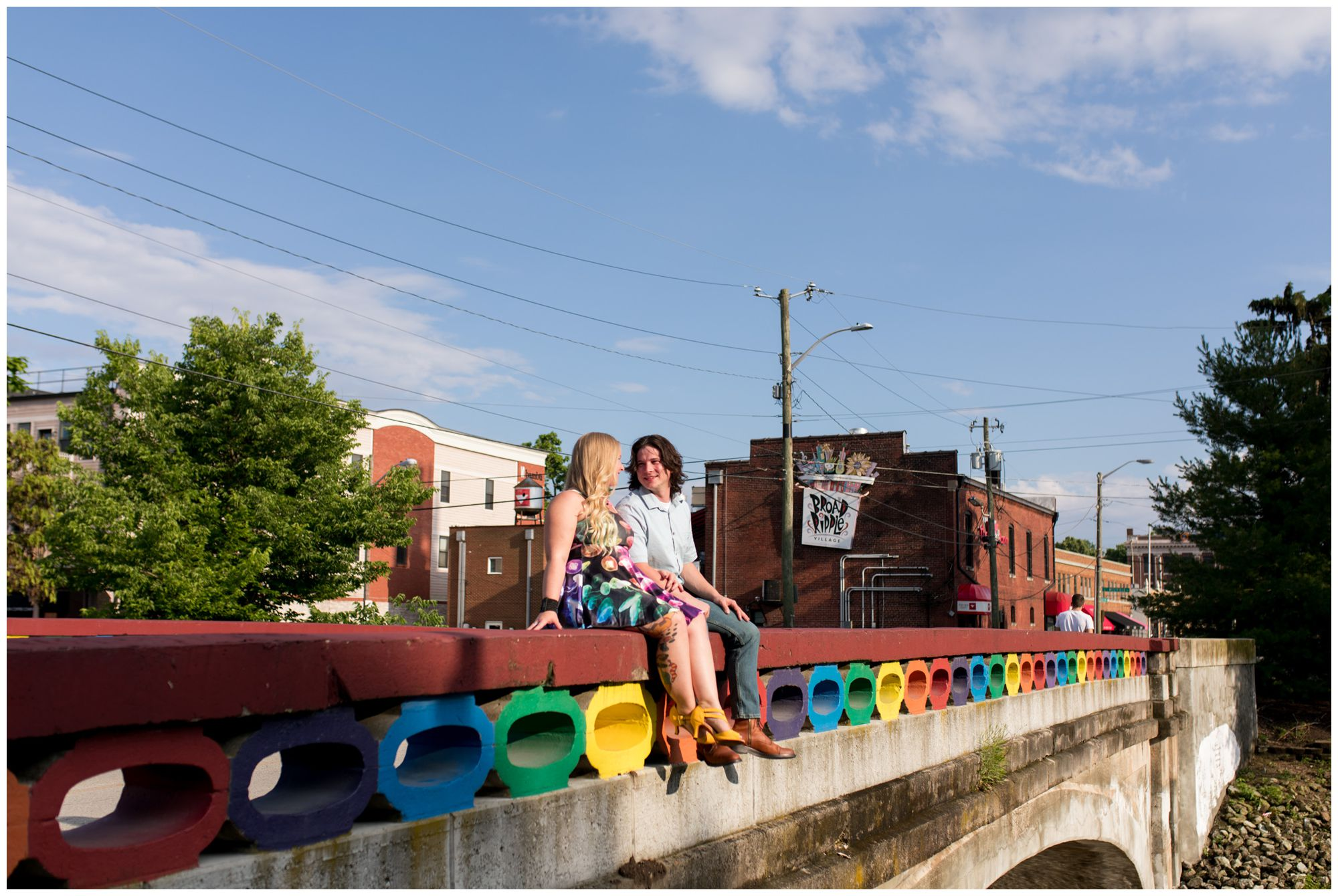 couple sitting on Rainbow Bridge in Broad Ripple during engagement session