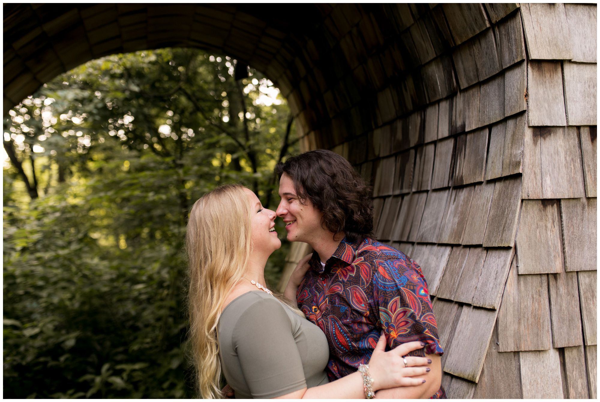 couple touch noses during engagement session in Broad Ripple