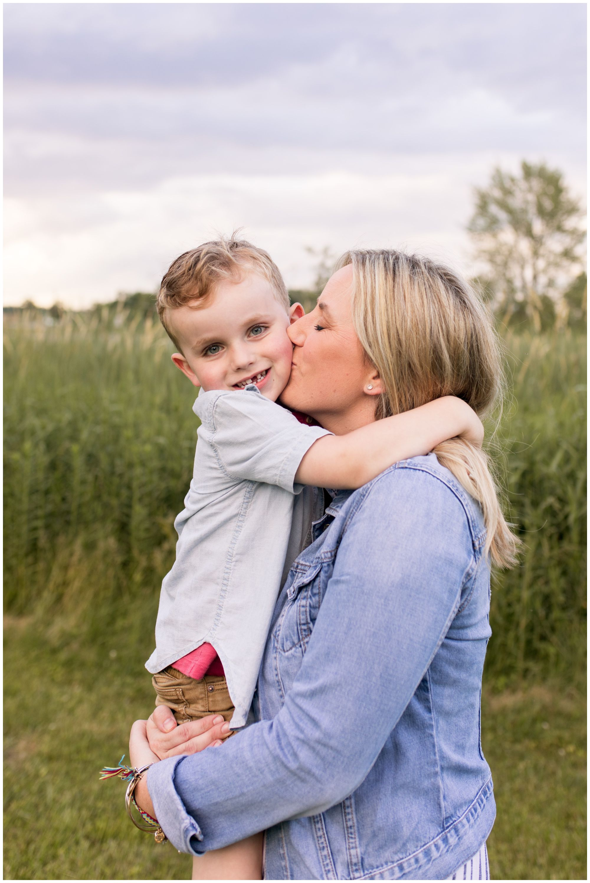 mom gives oldest son kiss on check during Kokomo Indiana family session