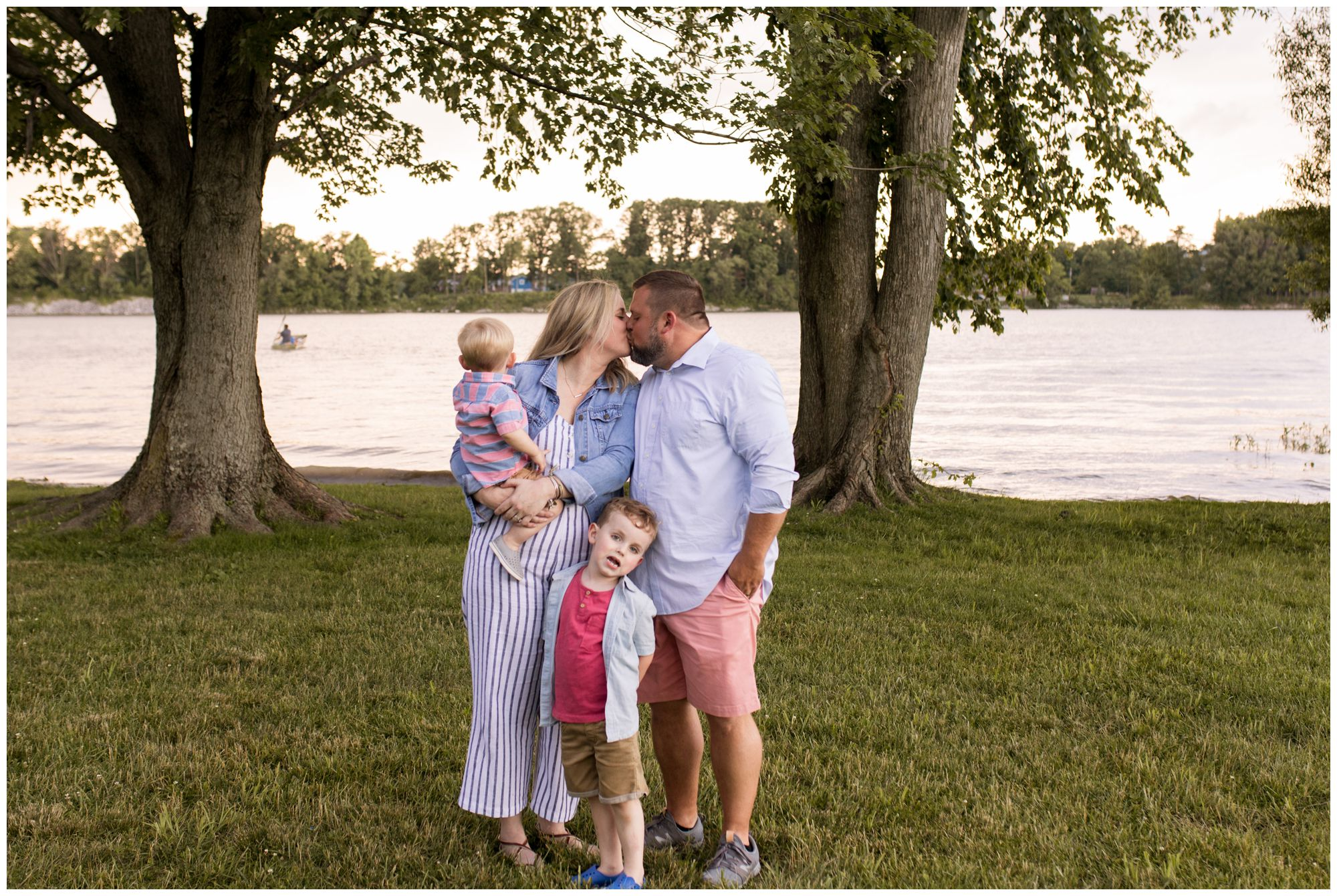 mom and dad kiss during family session at Wildkat Creek Reservoir Park in Kokomo Indiana
