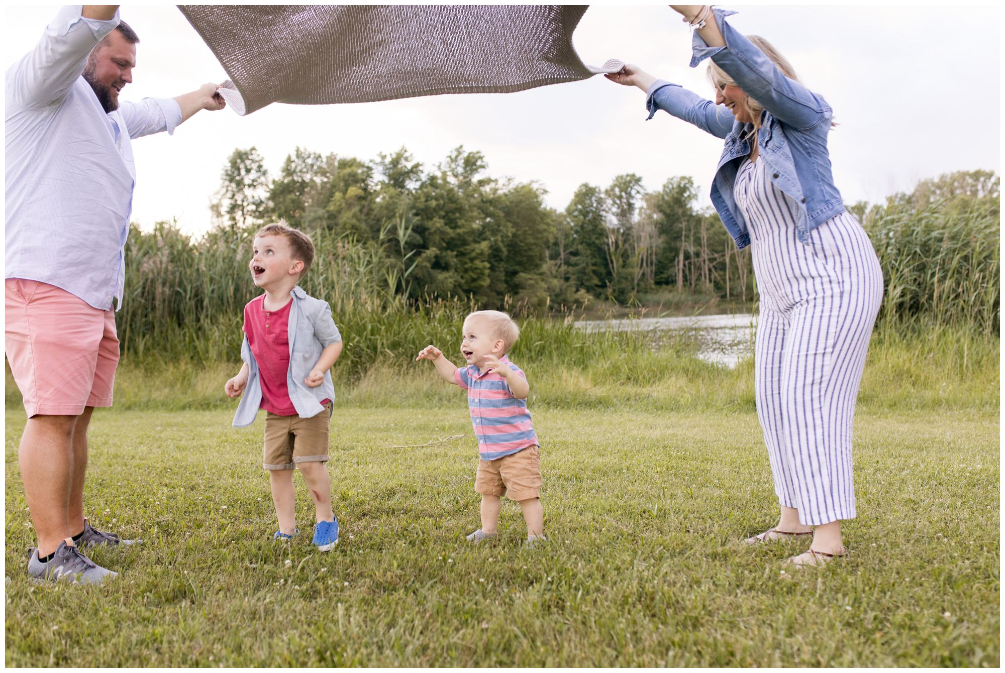 boys play under blanket with mom and dad during family session in Kokomo Indiana