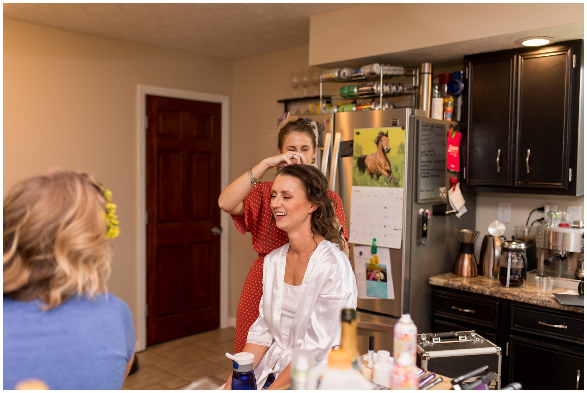 bride laughing while getting hair done in kitchen of Indianapolis wedding venue