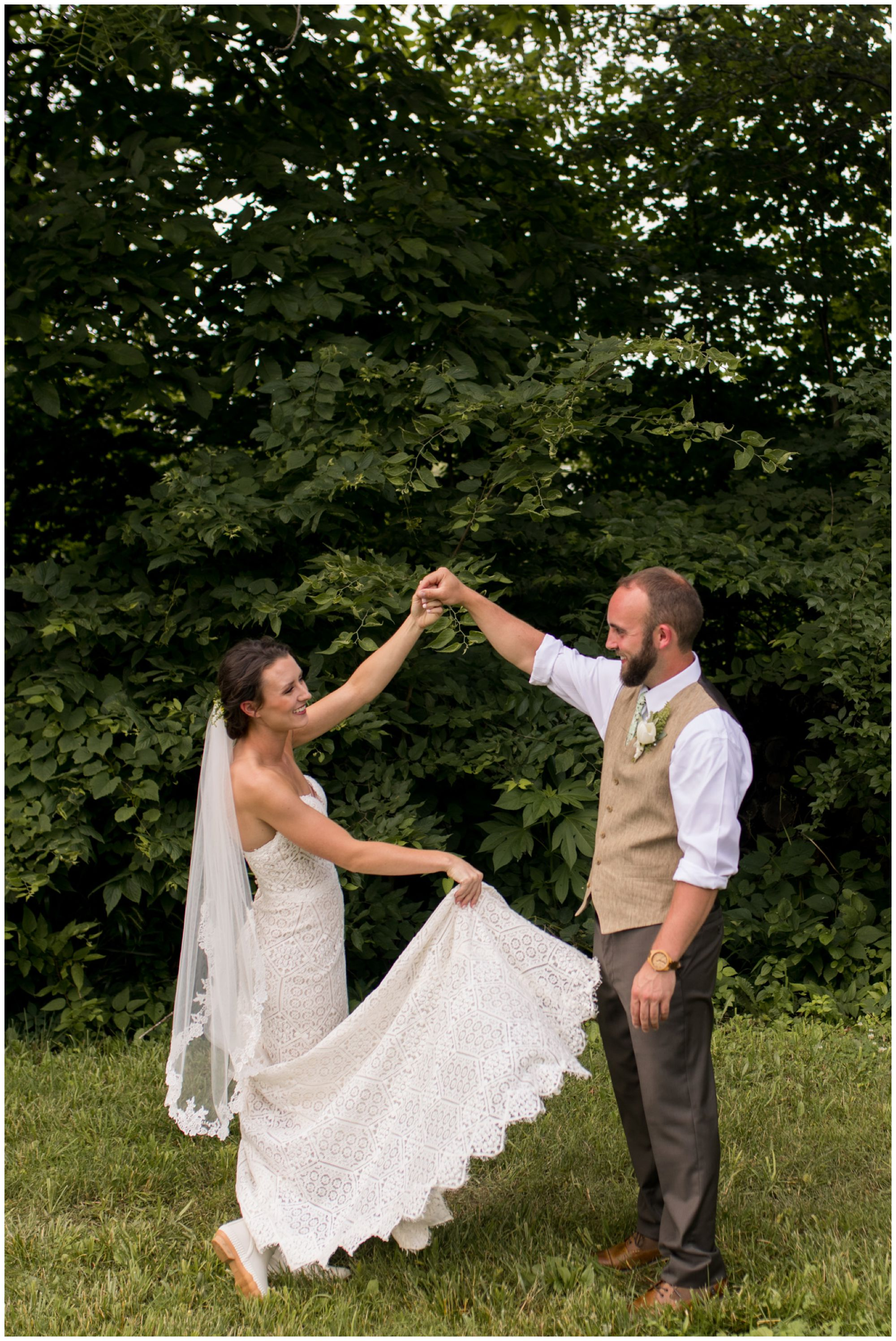 bride holds train of dress and spins during wedding couples portraits in Indianapolis