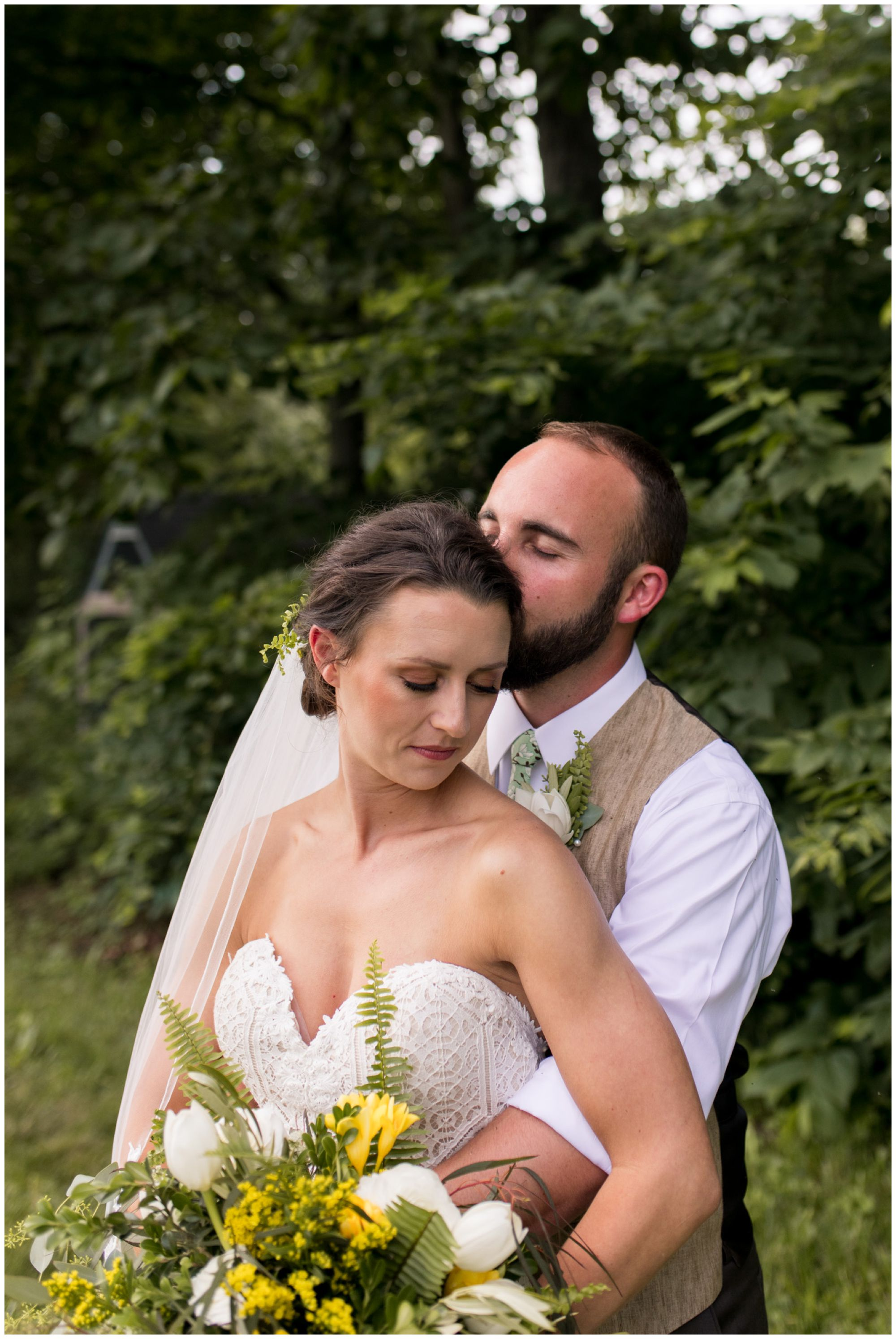 groom holds bride and kisses temple during Indianapolis wedding portraits