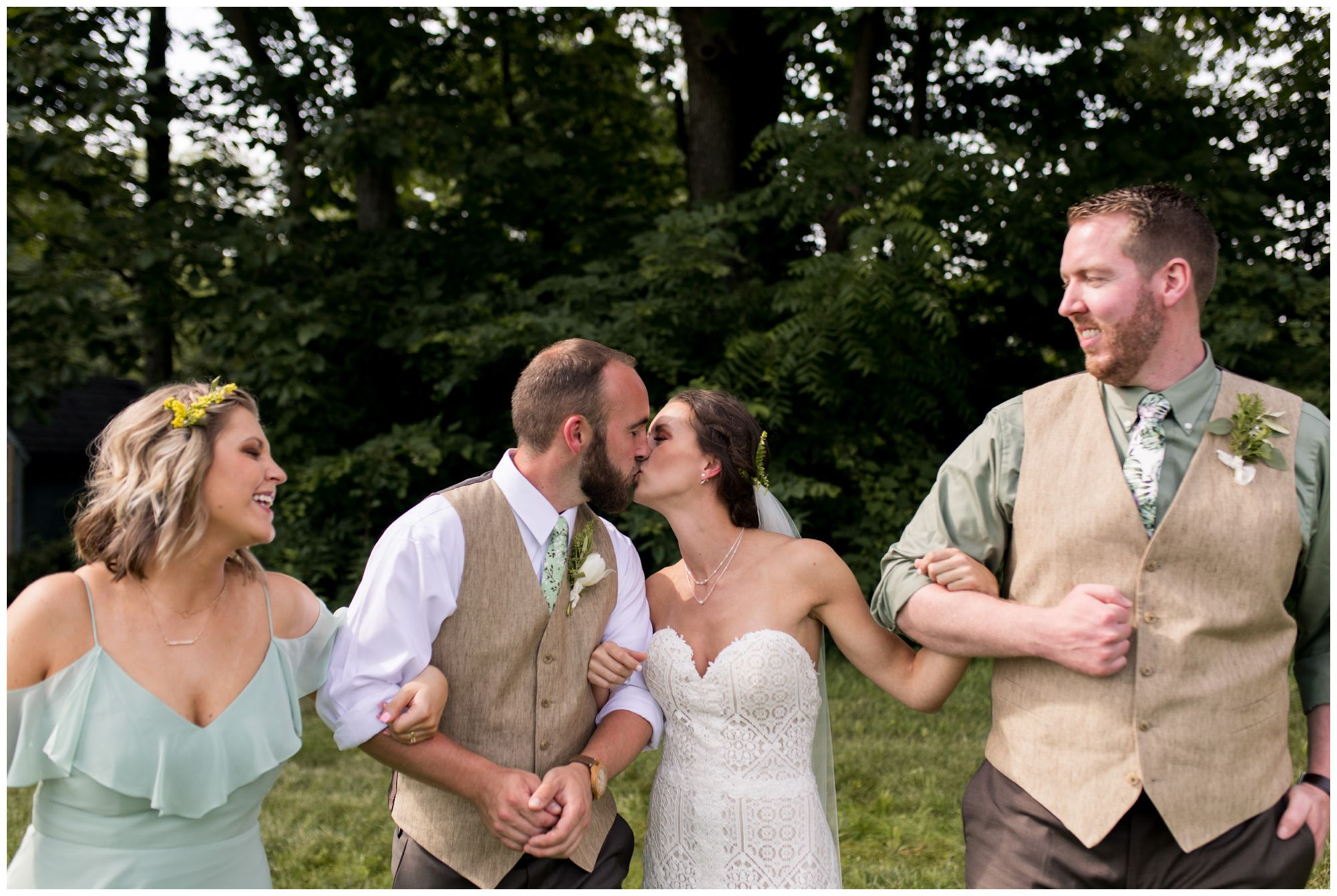 bride and groom kiss while wedding party walks in Indianapolis backyard wedding