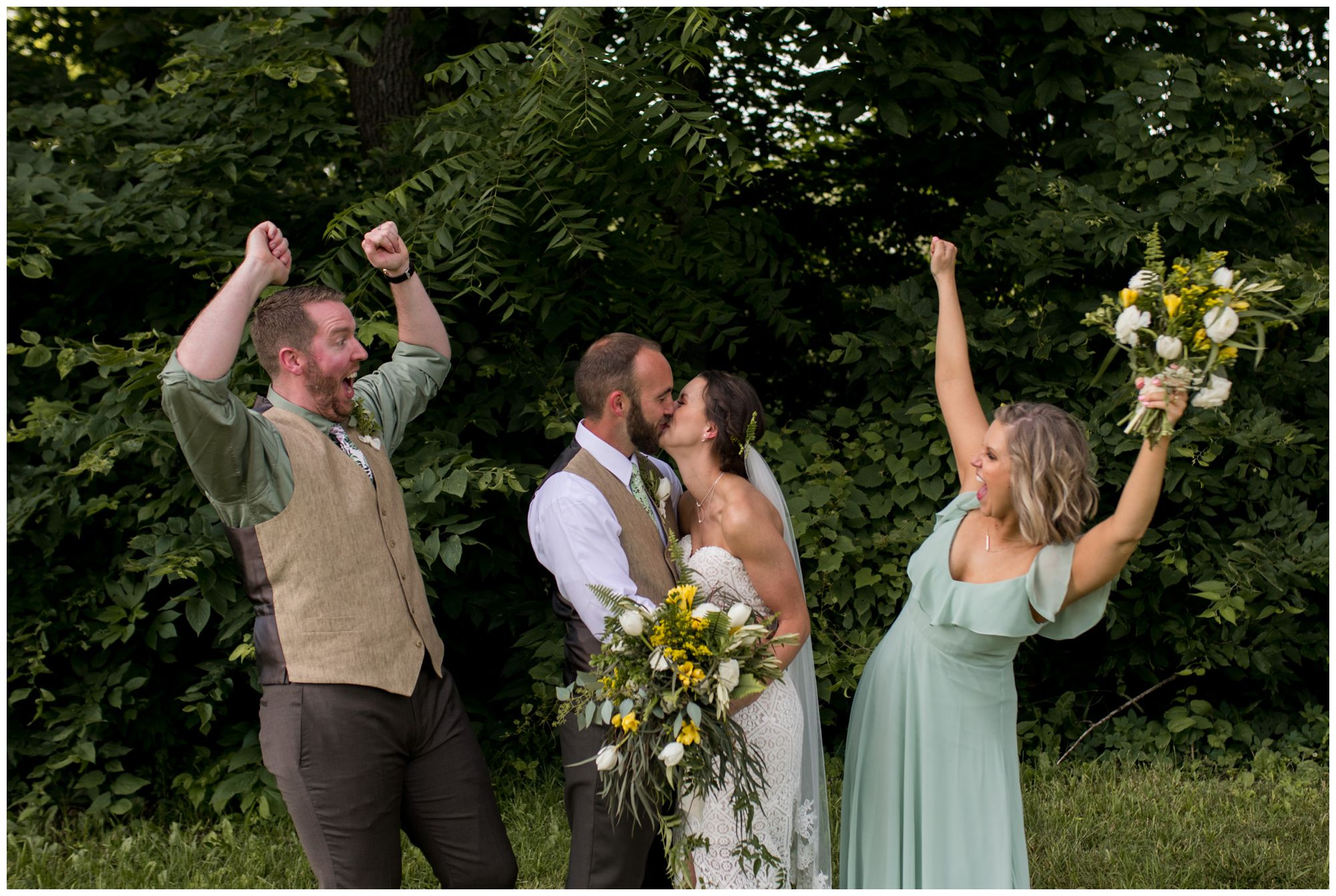 bride and groom kiss while wedding party cheers at Indianapolis backyard wedding