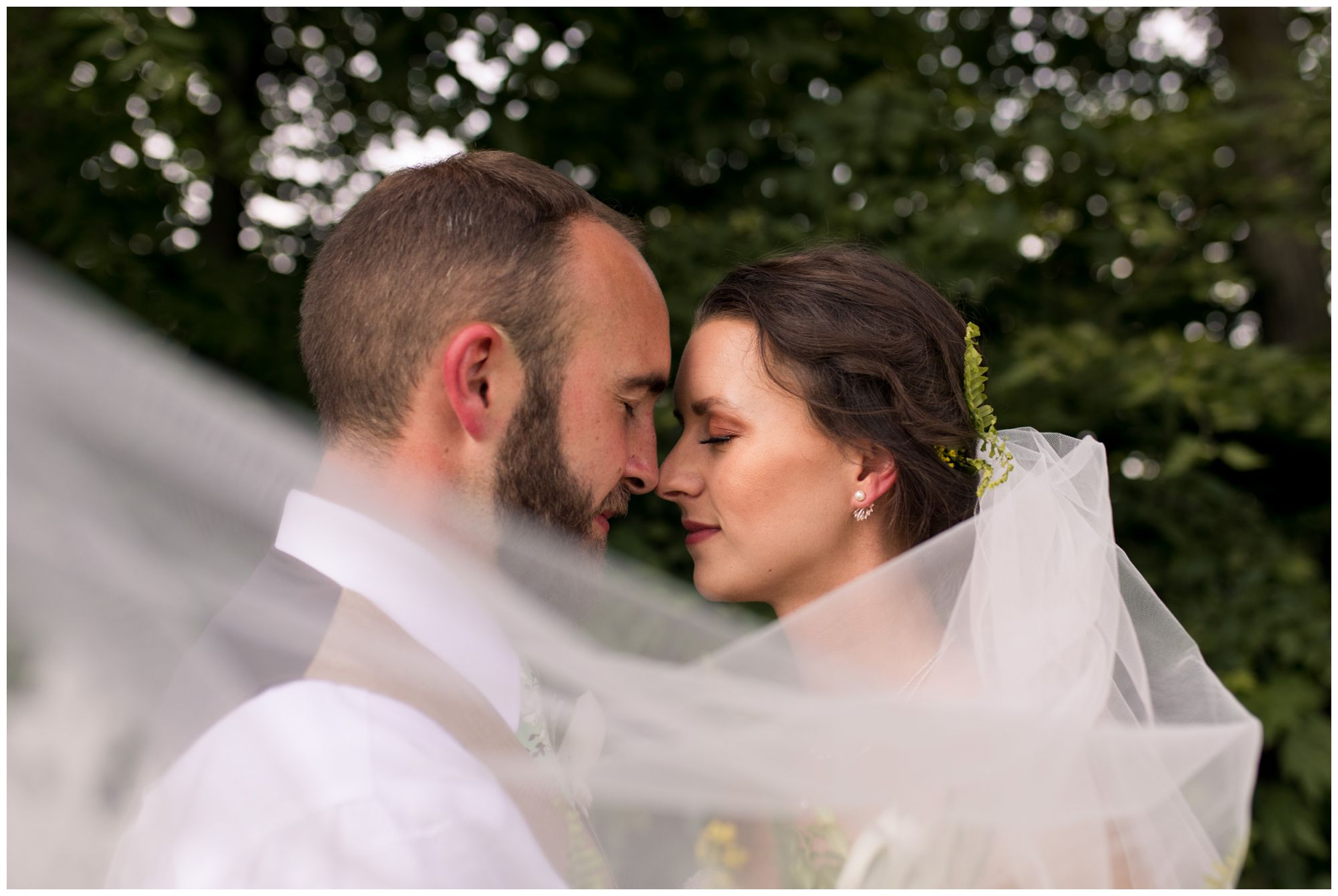 bride and groom with veil sweeping in front of couple at Indianapolis wedding