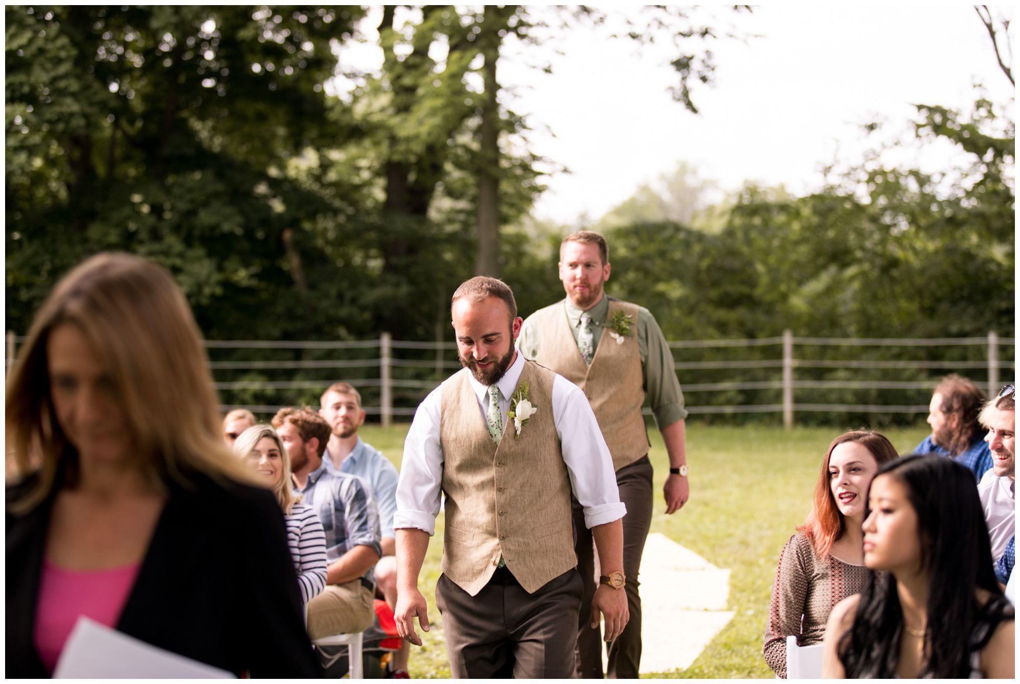 groom walks into wedding ceremony with best man behind