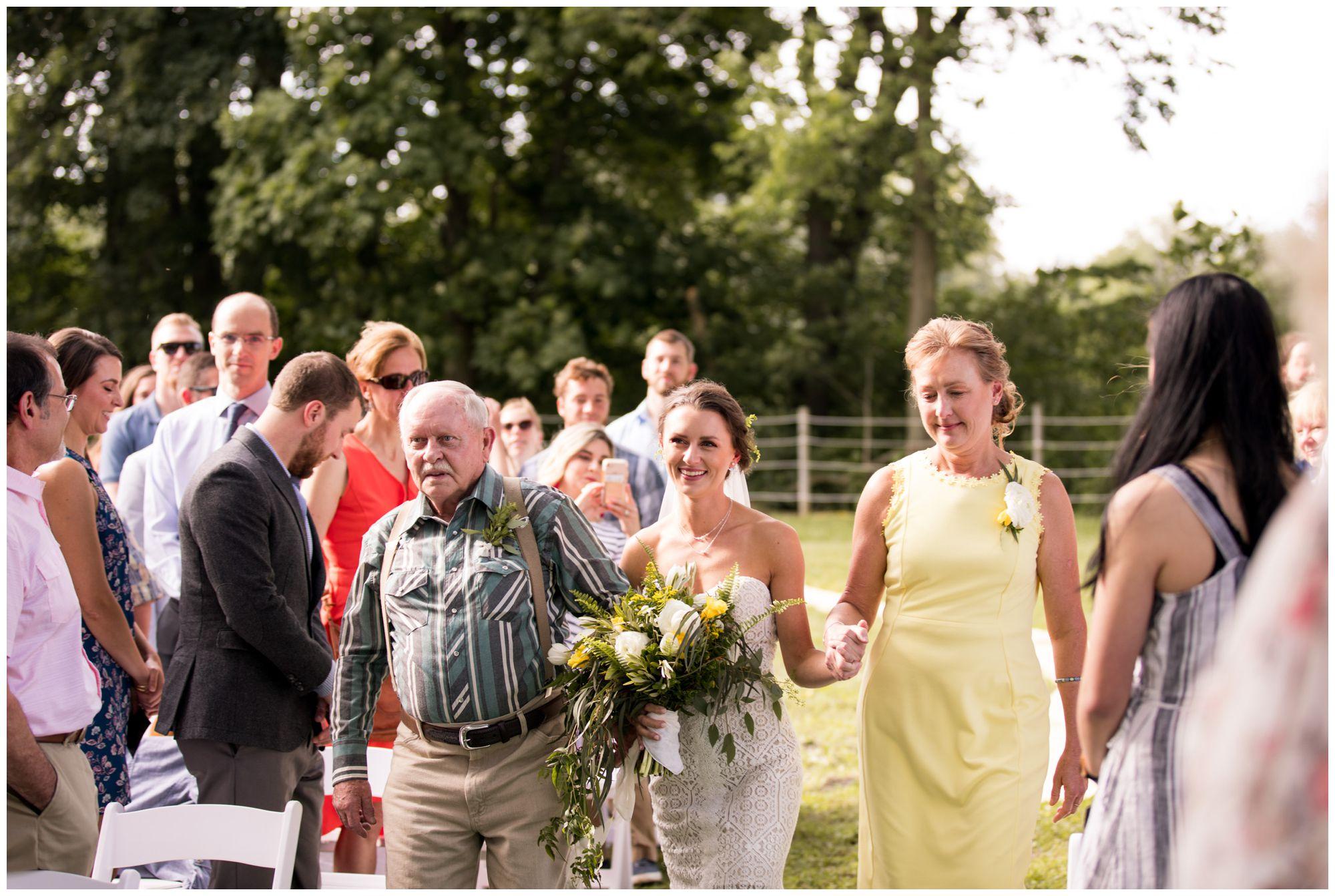 bride walks into Indianapolis wedding ceremony with mom and dad