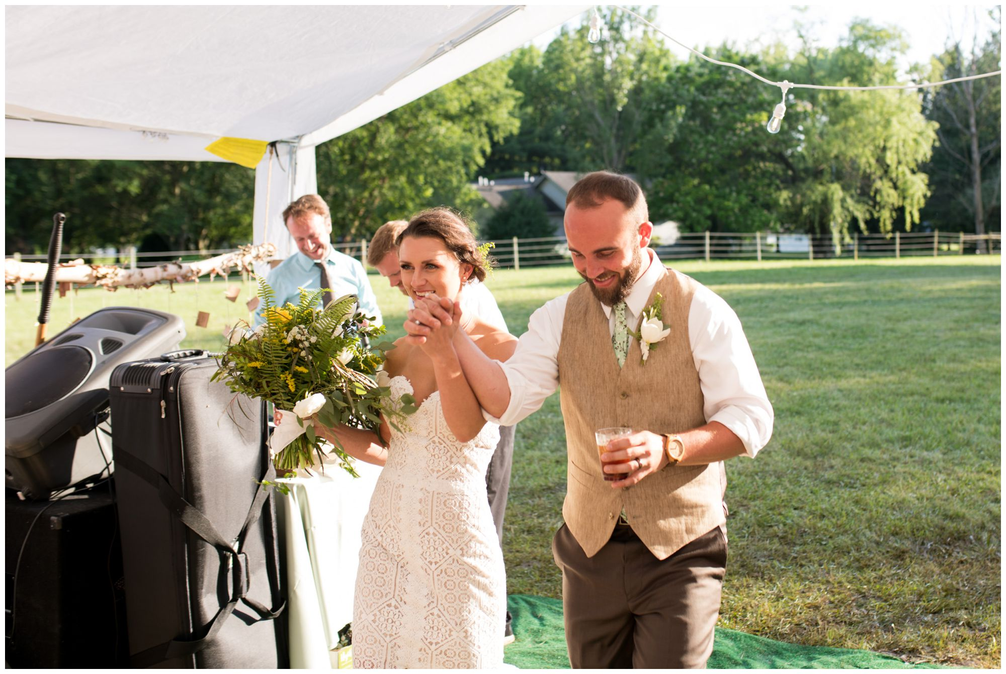 bride and groom walk hand in hand entering Indianapolis tented wedding reception
