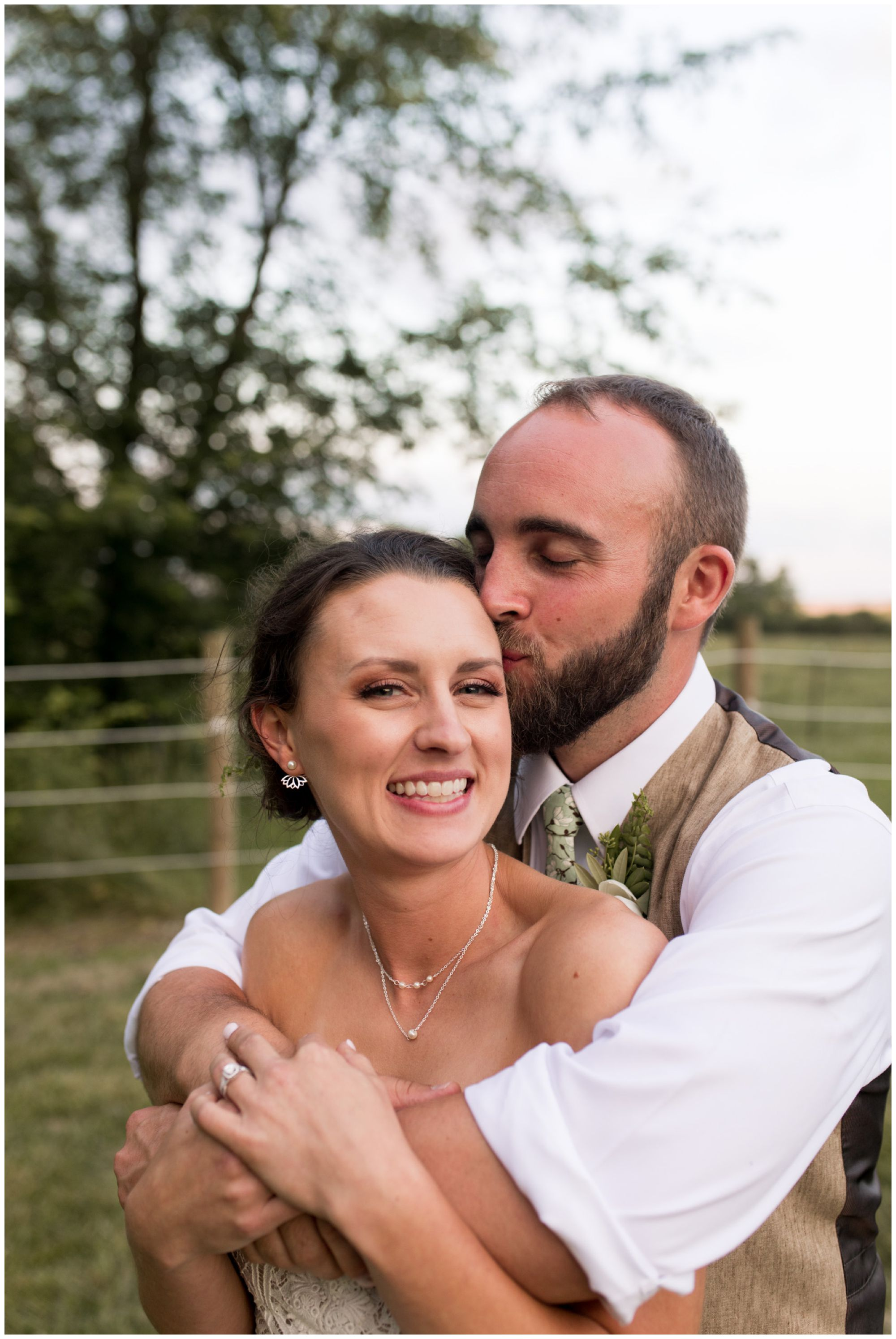 groom kisses bride's forehead as she grins during sunset portraits in Indianapolis