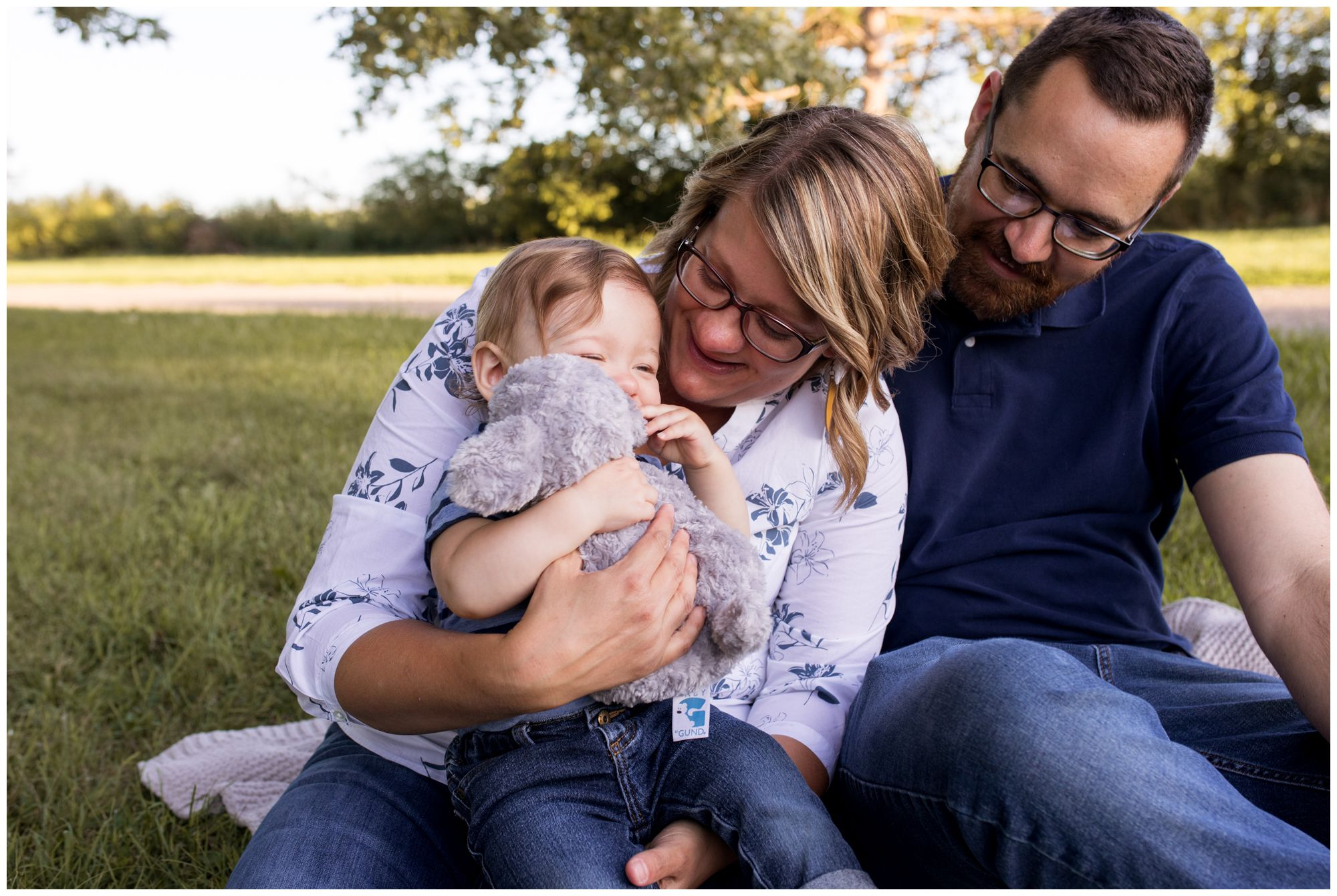 mom and dad play with son during Kokomo reservoir family session
