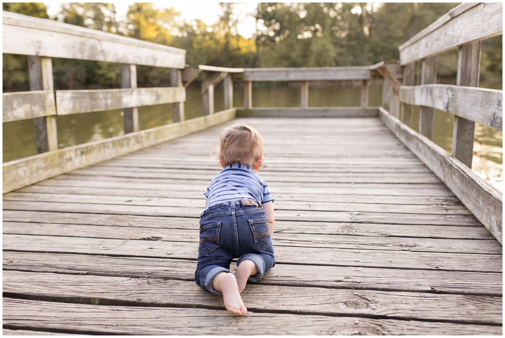 boy crawling on bridge during family session at Wildkat Creek Reservoir Park in Kokomo Indiana