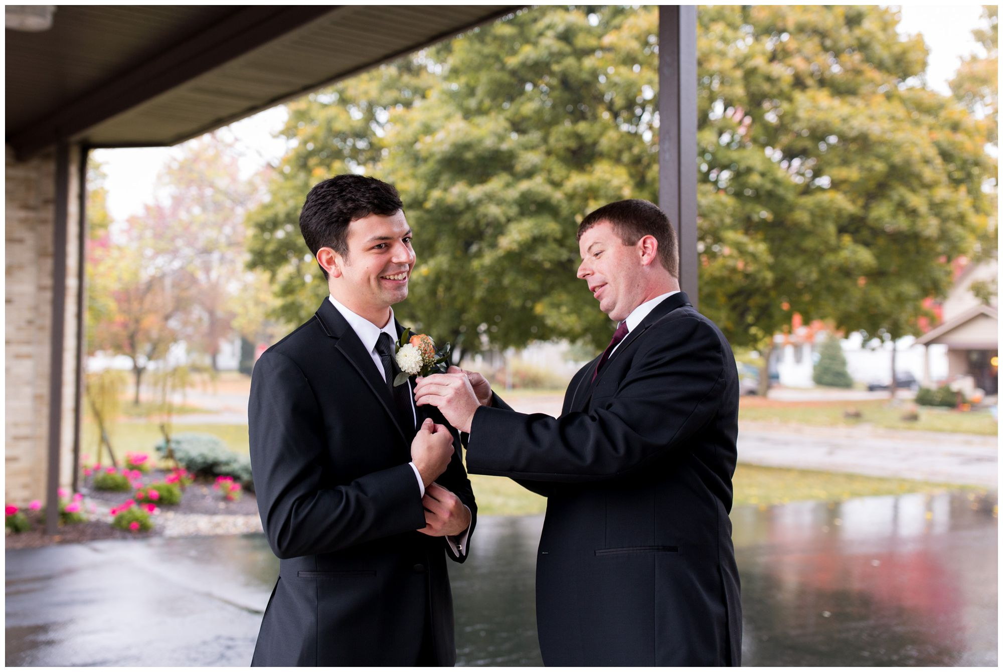 best man pins boutonniere to groom's jacket before first look at Zion Lutheran Church in Decatur Indiana