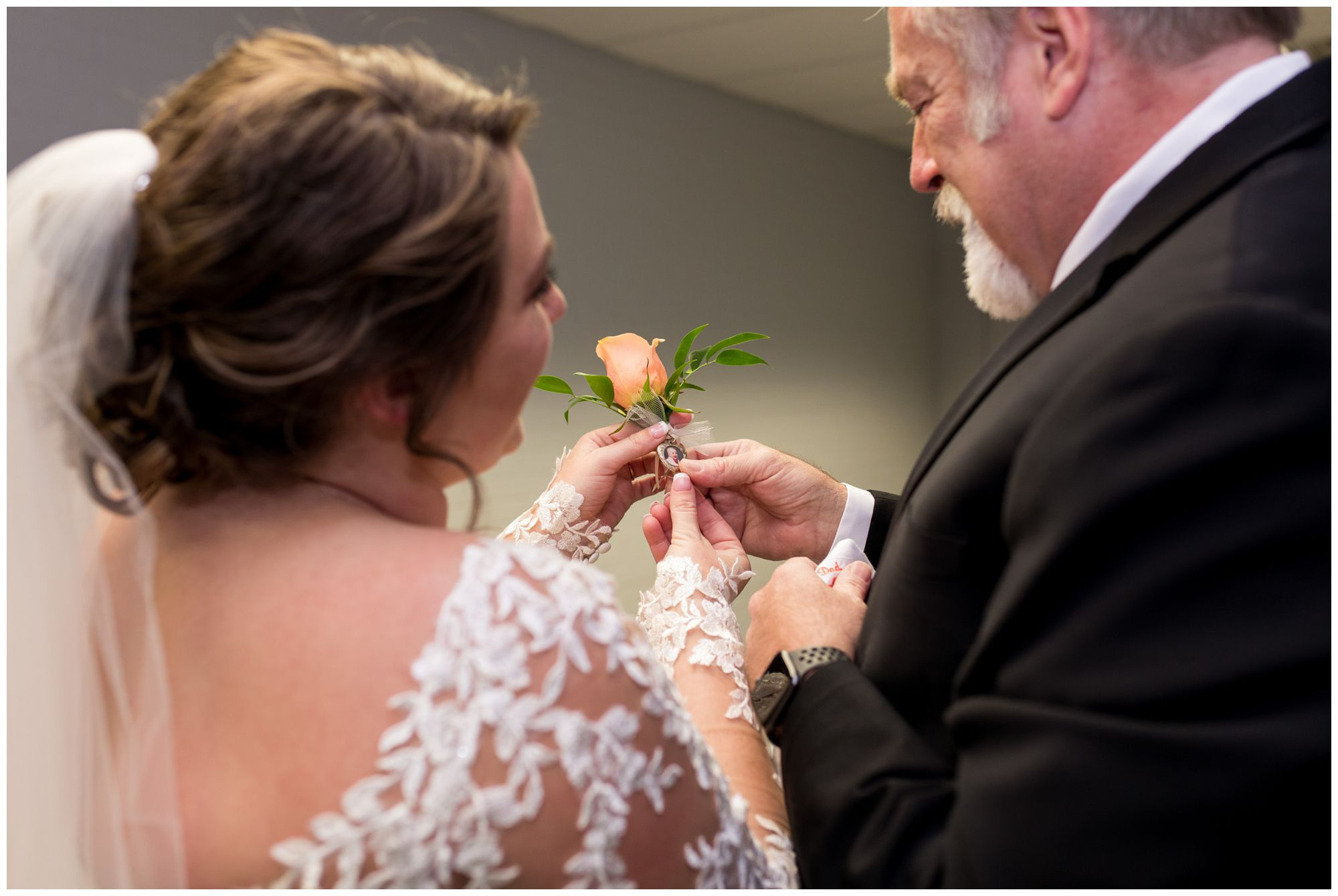 bride shows dad baby photo on boutonniere before wedding ceremony in Decatur Indiana