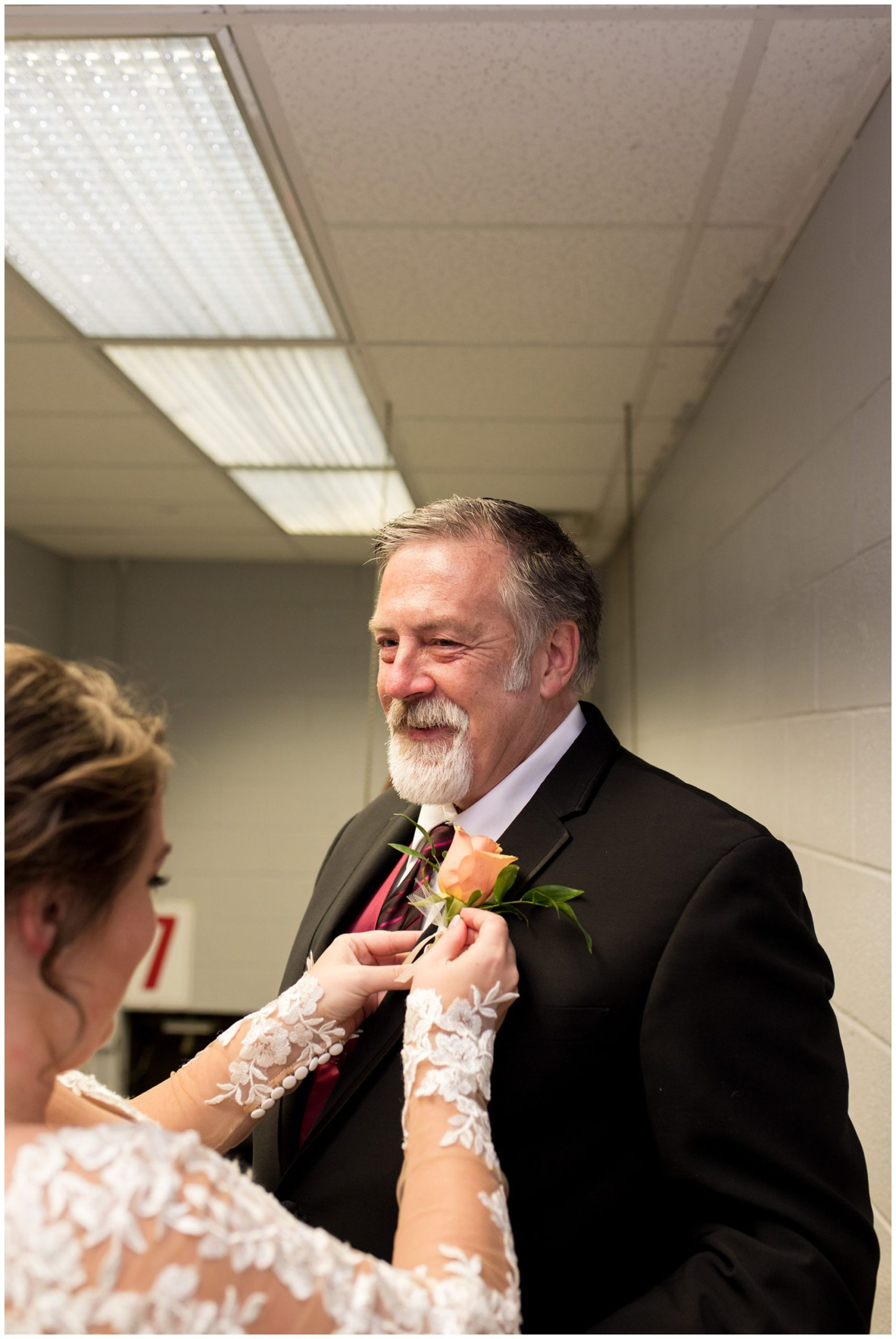 bride pins boutonniere on dad's jacket before Zion Lutheran Church wedding