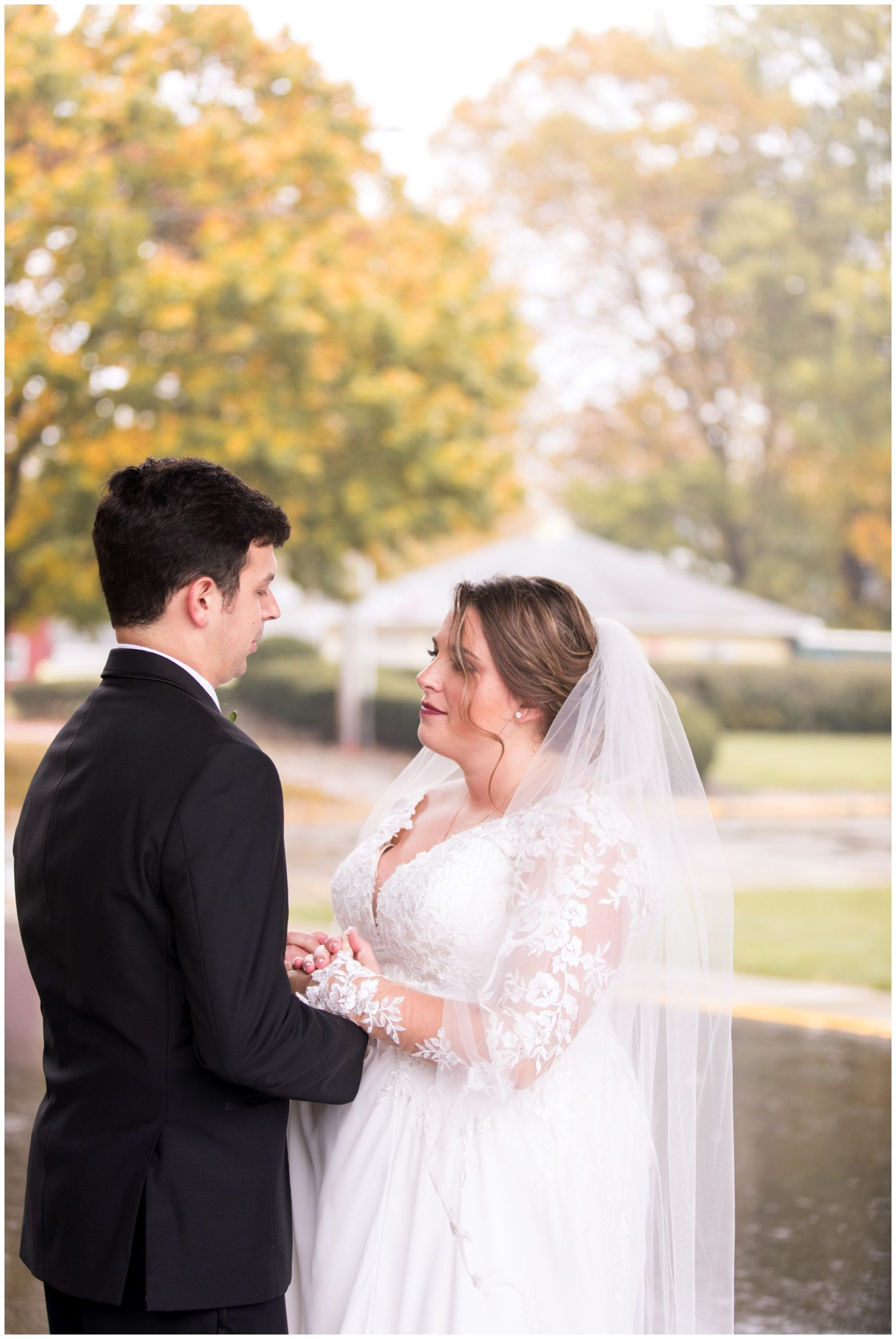 bride and groom hold hands after first look and pray together