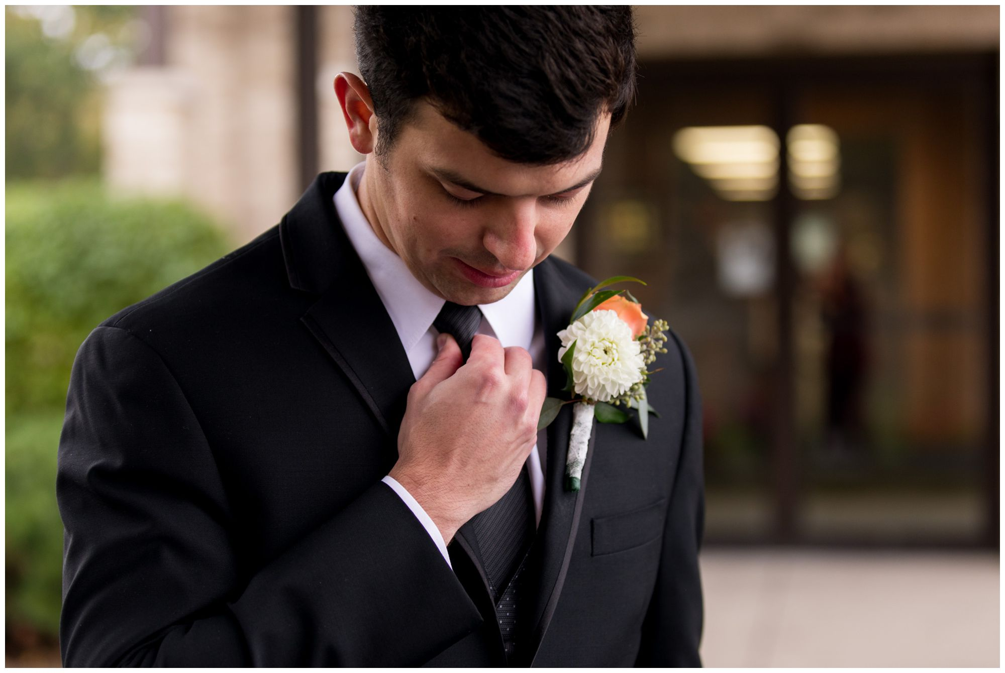 groom straightens tie before wedding ceremony at Zion Lutheran Church in Decatur Indiana